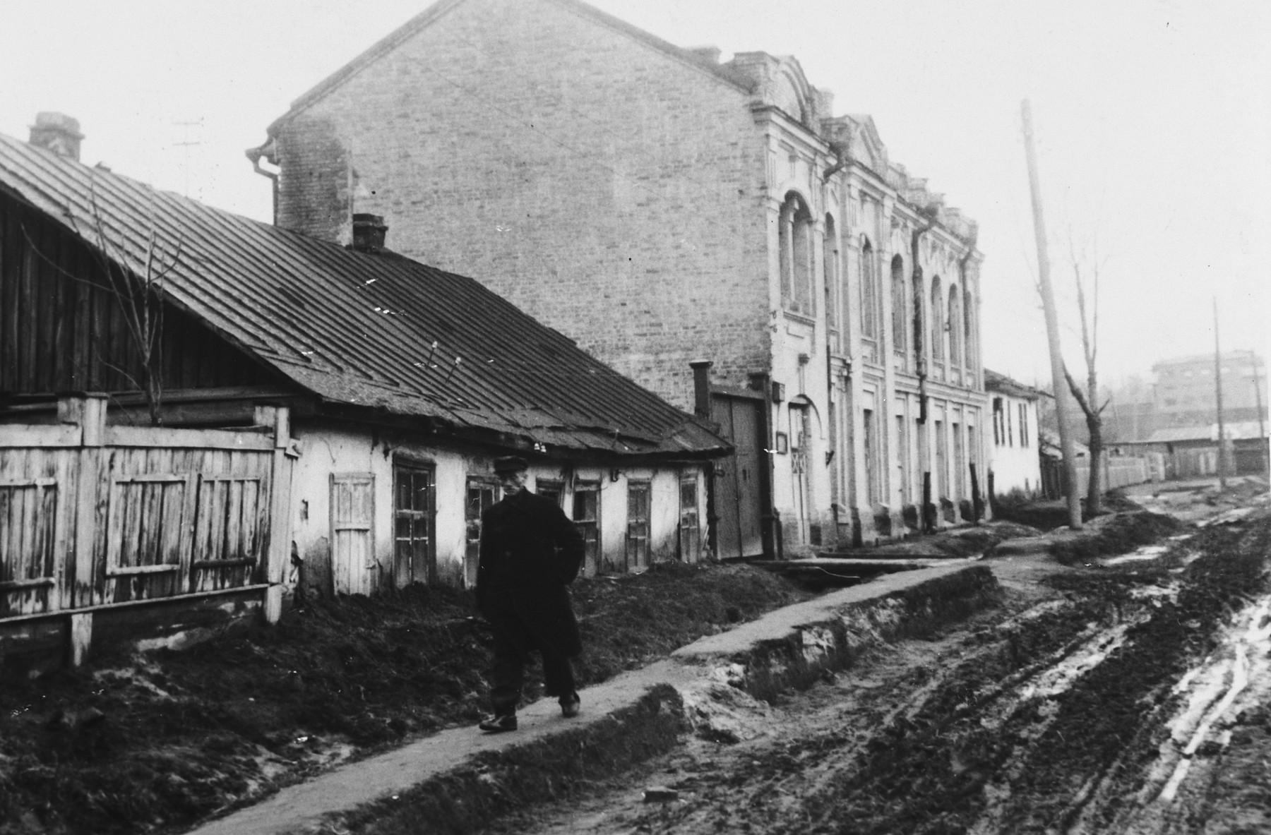 "A man walks down a muddy street of an unidentified town under German occupation.  The caption of the SS-Archiv says Haupteinfahrtstrasse nach der Stadt (...) Okt. 1941"" (main entrance street to the city (...) Oct. 1941)."