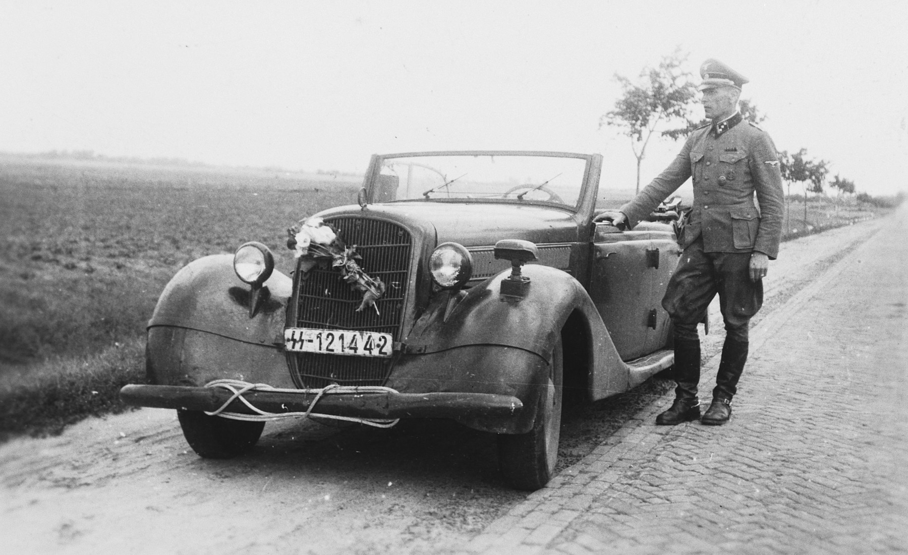 "A SS officer [perhaps Max Schmidt] stands next to an automobile with an SS license plate.   The caption of the SS-Archiv says ""Abschied vom Osten, auf der Fahrt ins Reich - Juli 1942"" (Parting from east, on the trip to the ""Reich"" July 1942)."