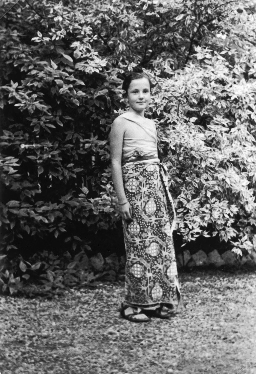Close-up portrait of a German-Jewish girl dressed in a Balinese costume while visiting her grandparents in a summer home outside of Riga.  Pictured is Mara Vishniac, daughter of the photographer Roman Vishniac.  Her aunt had studied in Bali and brought back the costume.