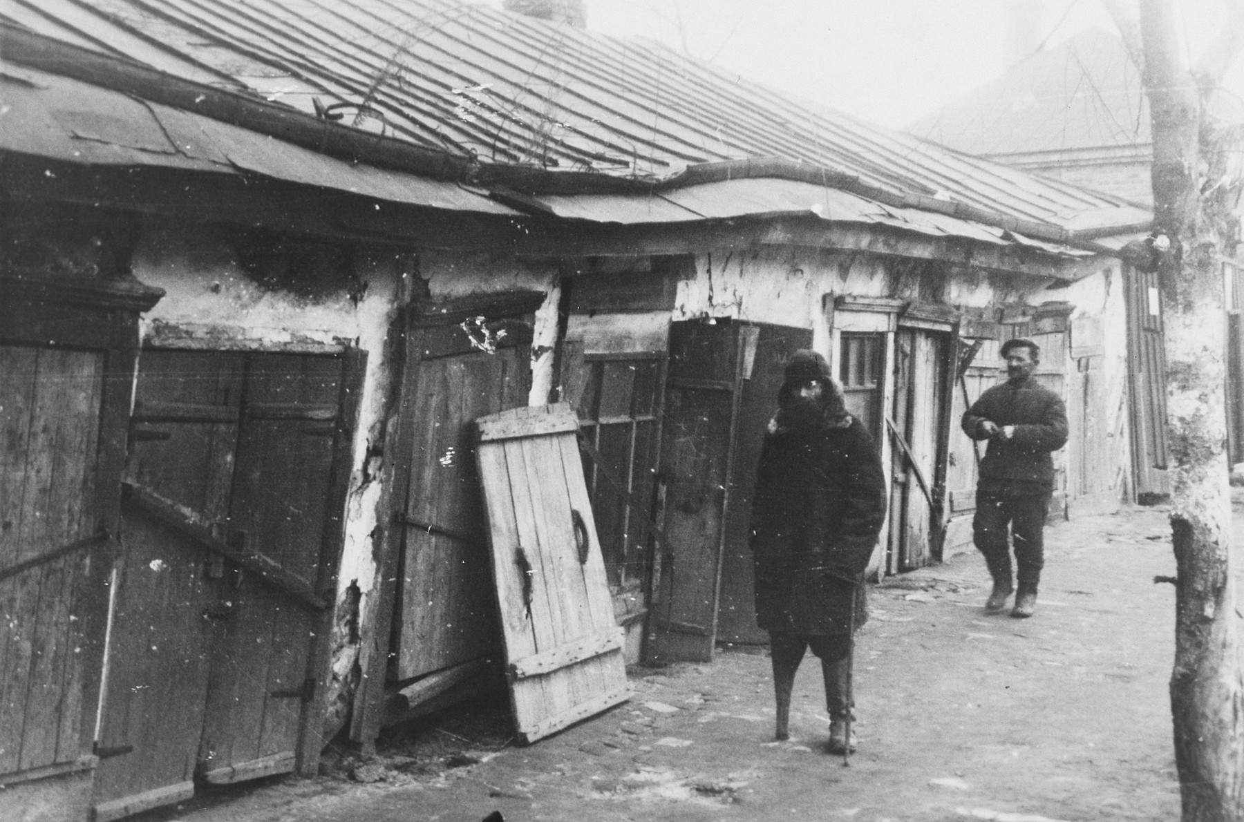 "Two Jewish men walk down a street in front of a shuttered, rickety building.  The caption of the SS-Archiv says ""Arbeiterhaeuser in Garkono (?) Okt. 1941"" (Workerhouses in Garkono (?) Oct.1941)."