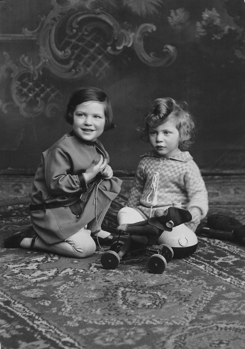 Lore and Erich Rothheimer sit on an oriental rug next to a toy airplane.