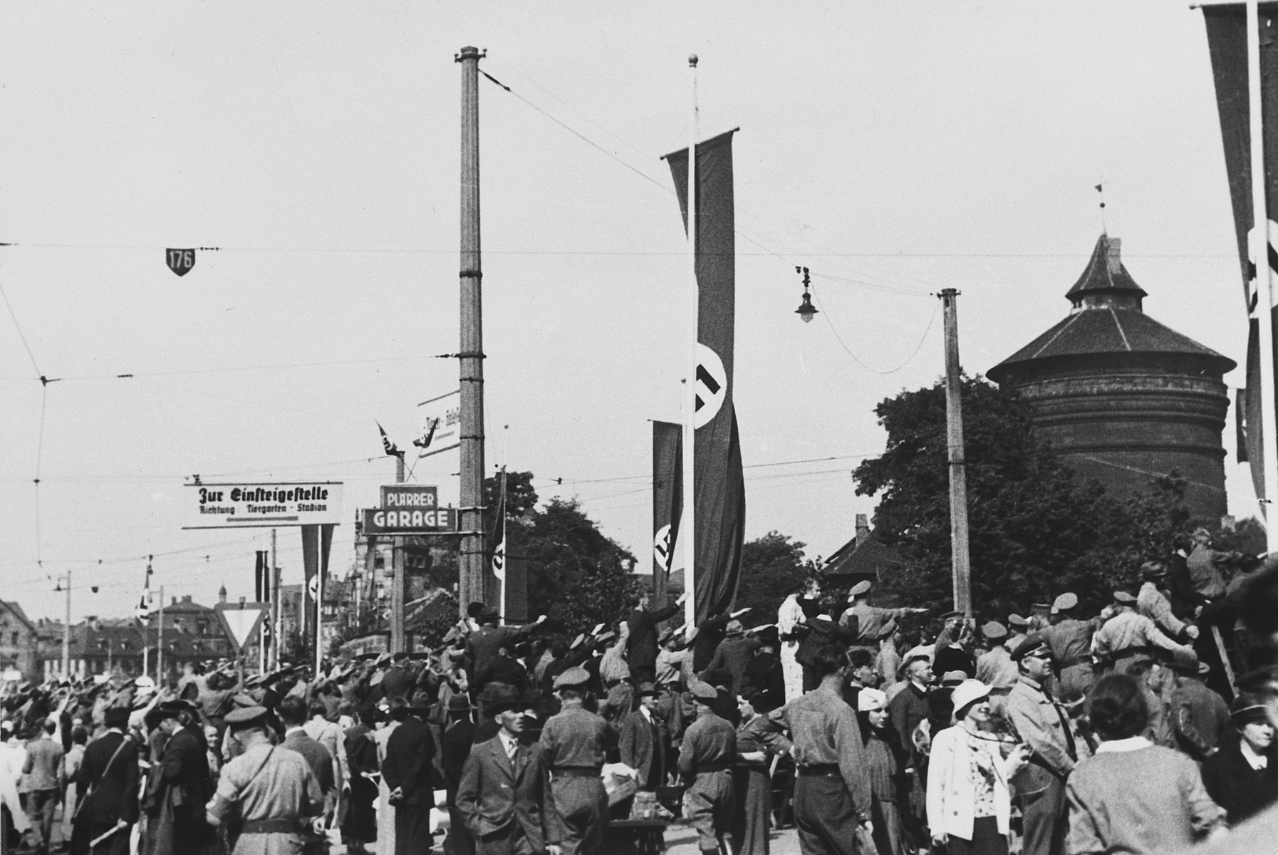 German citizens crowd together on a street in Nuremberg bedecked with Nazi flags.  This photograph was taken by a German Jewish woman, Lilli Rahn, who later emigrated.