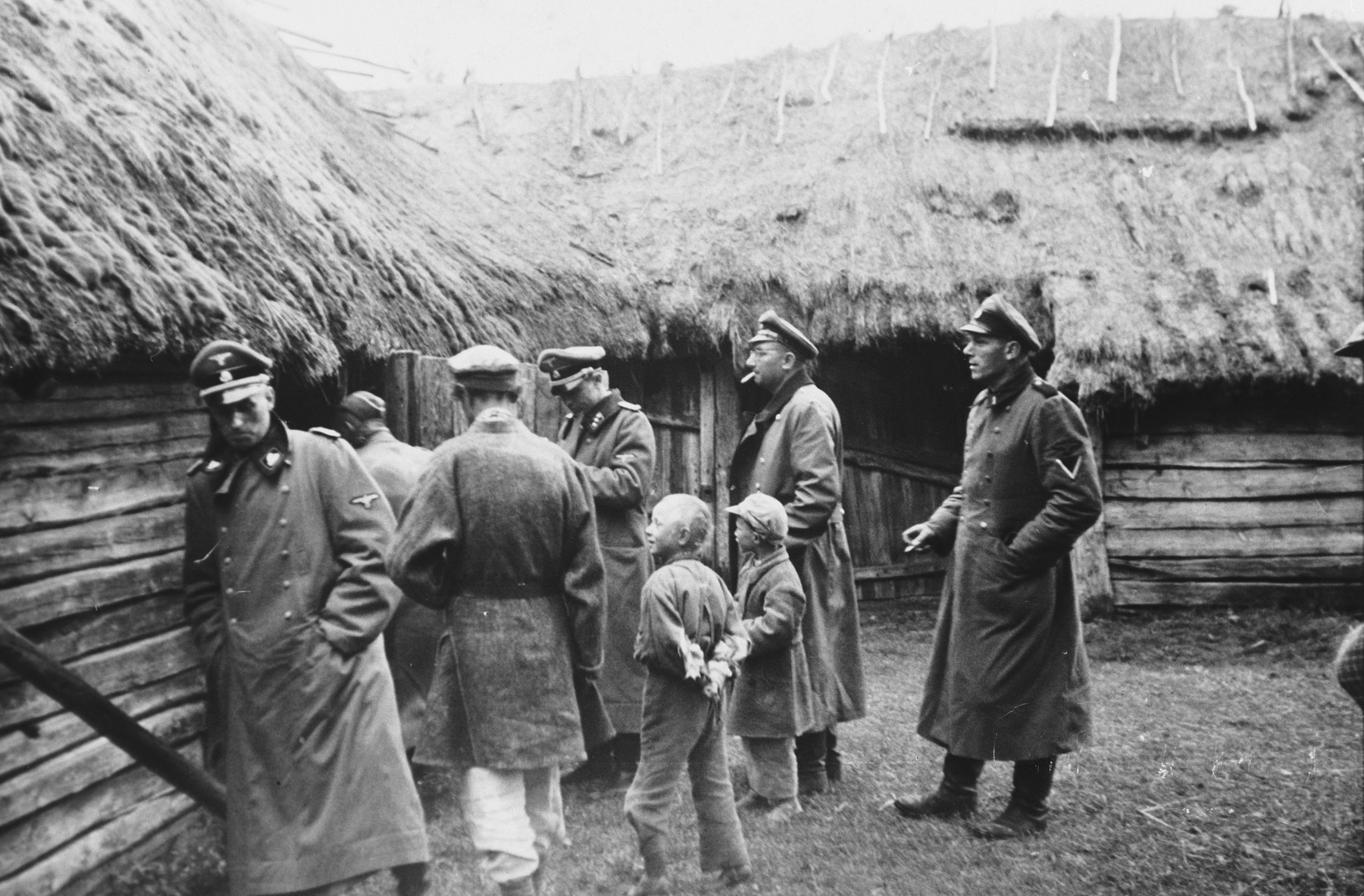 "SS officers inspect Russian farmhouses while two children and a civilian look on.  The caption of the SS-Archiv says ""Russische Bauernhaeuser in der Prim Okt. 1941"" (Russian farmhouses in the Prim October 1941)."