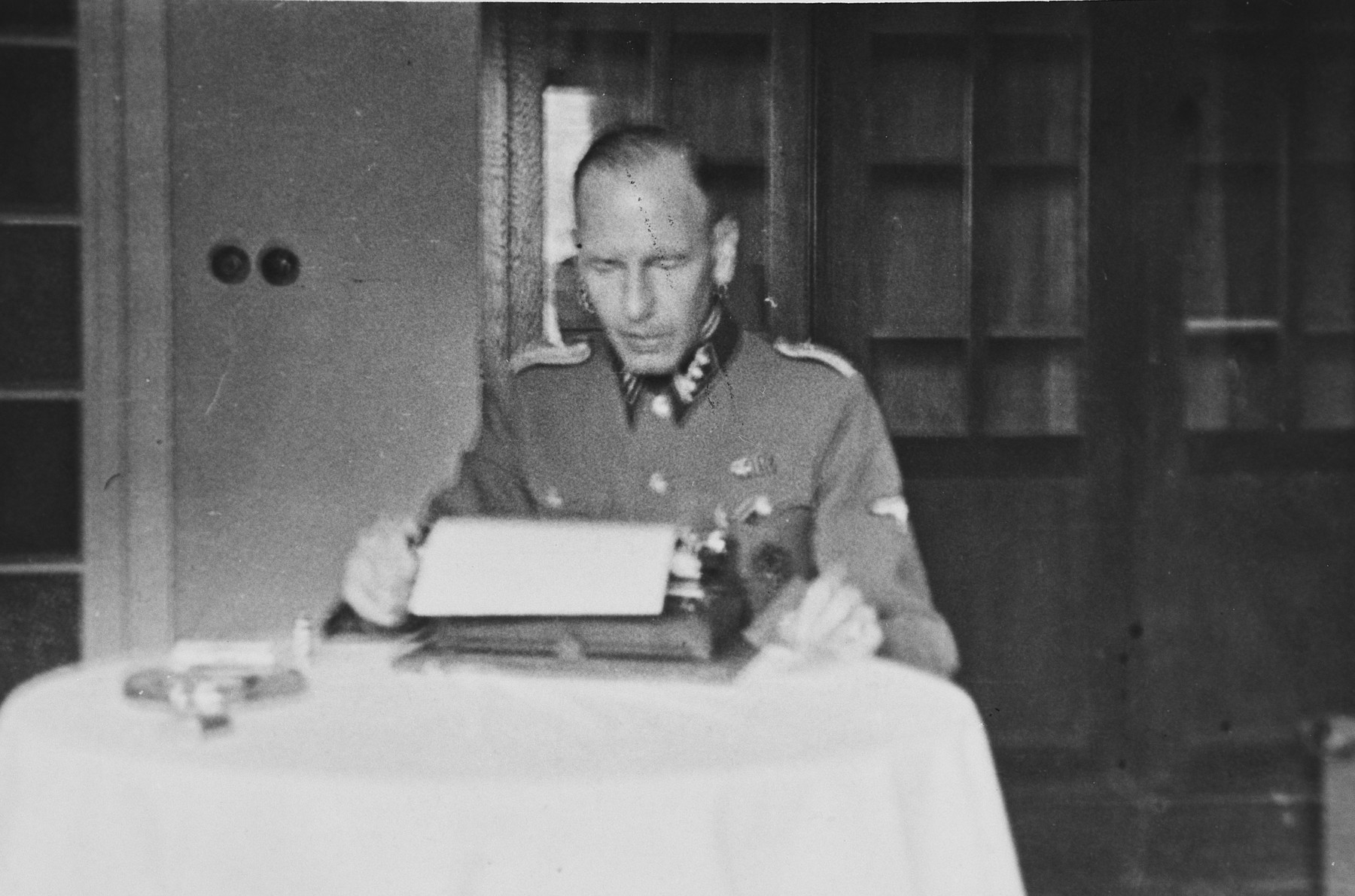 """A SS officer [perhaps Max Schmidt] works at his typewriter.   The caption of the SS-Archiv says """"Im Osten (...) Maerz 1942"""" (In the east (...) March 1942""""."""
