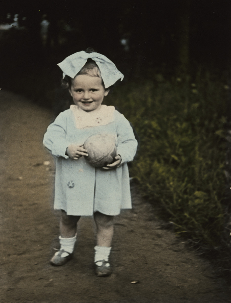 Close-up, colorized portrait of a  young Polish-Jewish toddler with a large bow and a ball.  Pictured is Sala Perec.