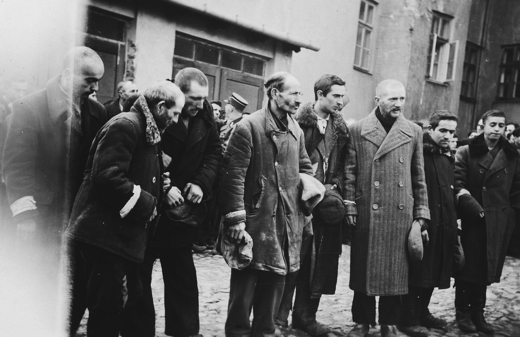 Jewish men are forced to stand in a line holding their hats in their hands [perhaps right after having had their beards forcibly shaven].