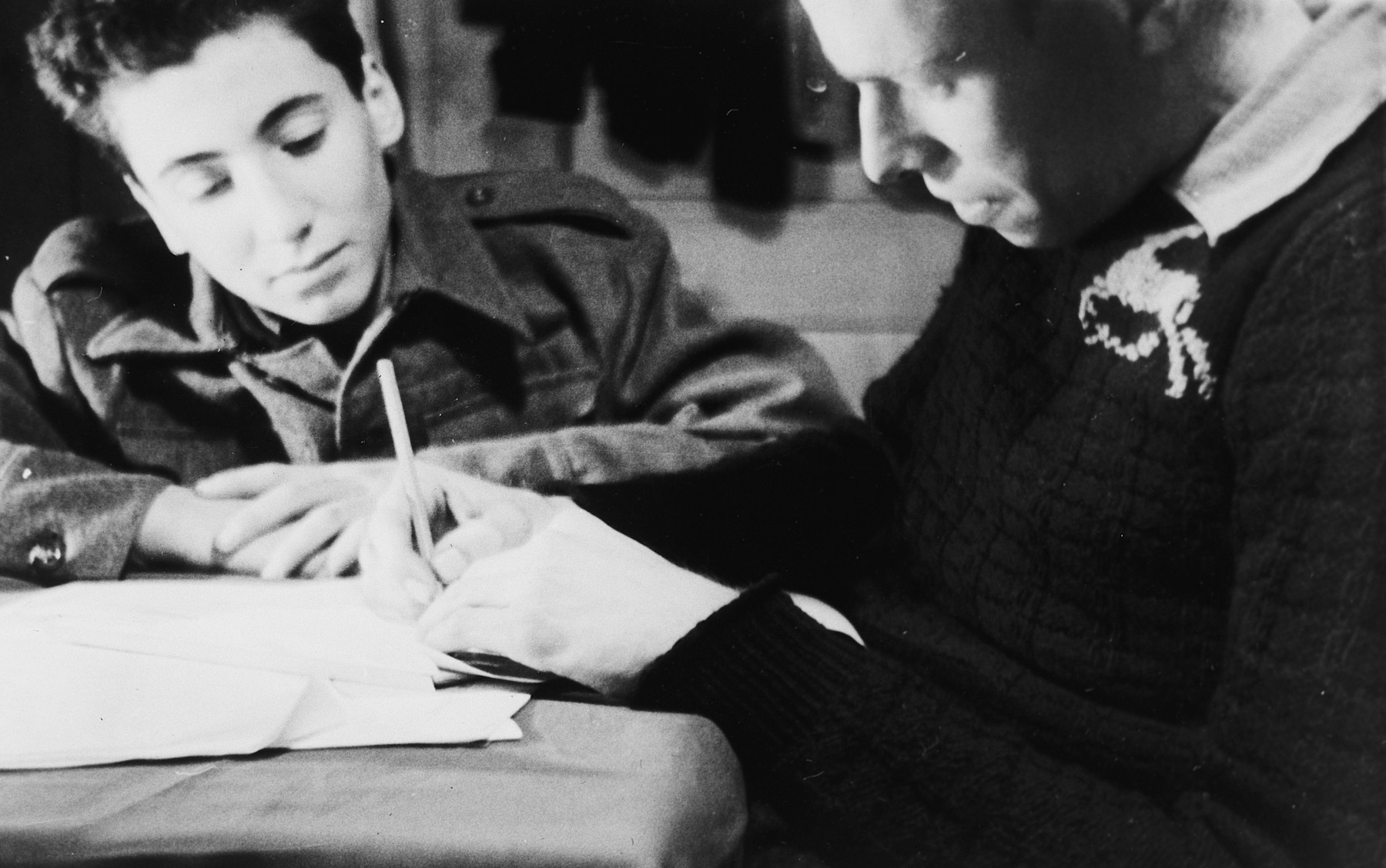 Two teenage boys write in a notebook in a boarding school in Switzerland.  Pictured is Stefan Polgar, a survivor from Hungary and the donor's roommate.