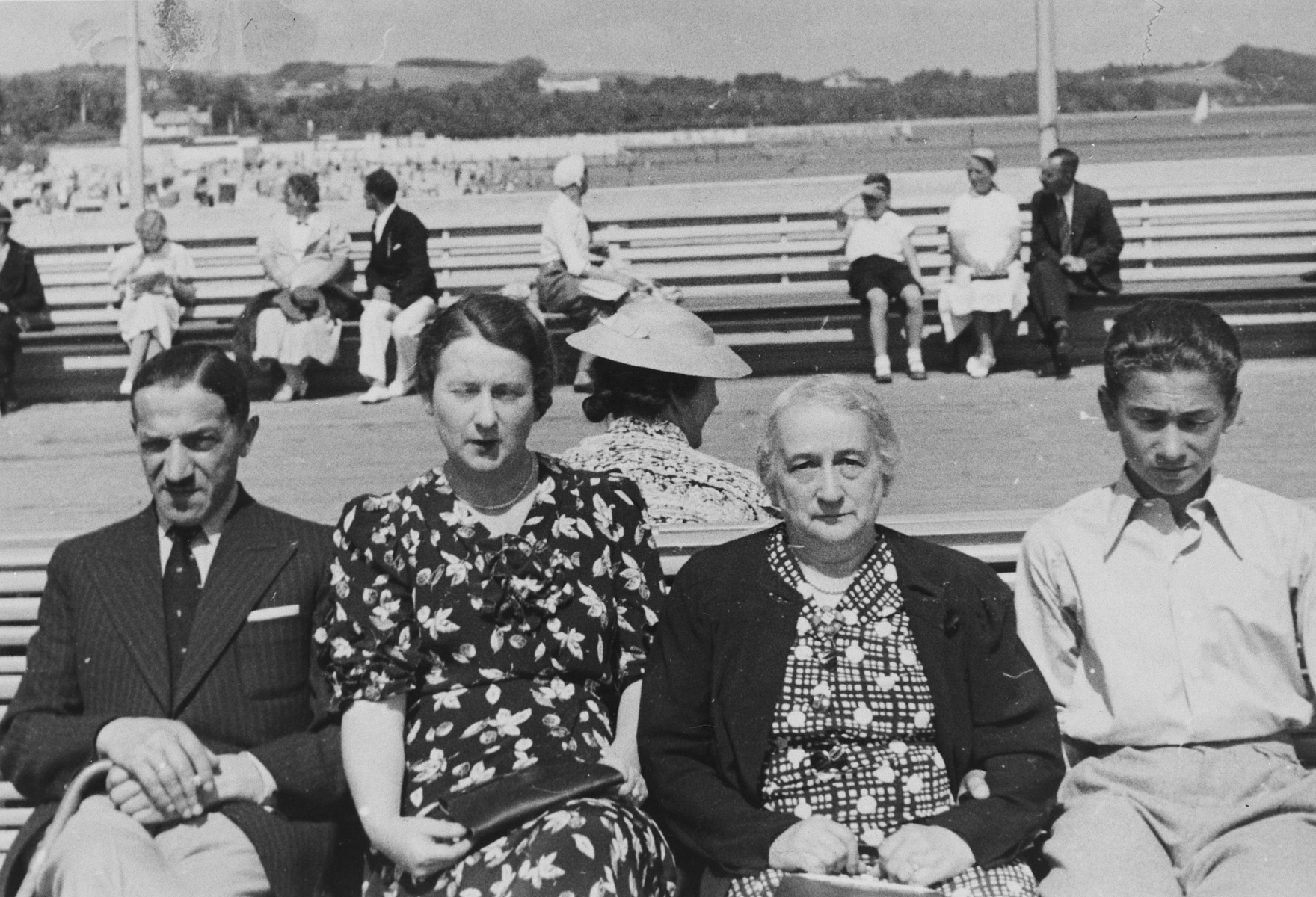 A Polish-Jewish family poses on outdoor benches while on vacation in Sopot.  Pictured from left to right are Julian Ratner, Gustava Ratner, Berta Szrajer, and Marjan Ratner.