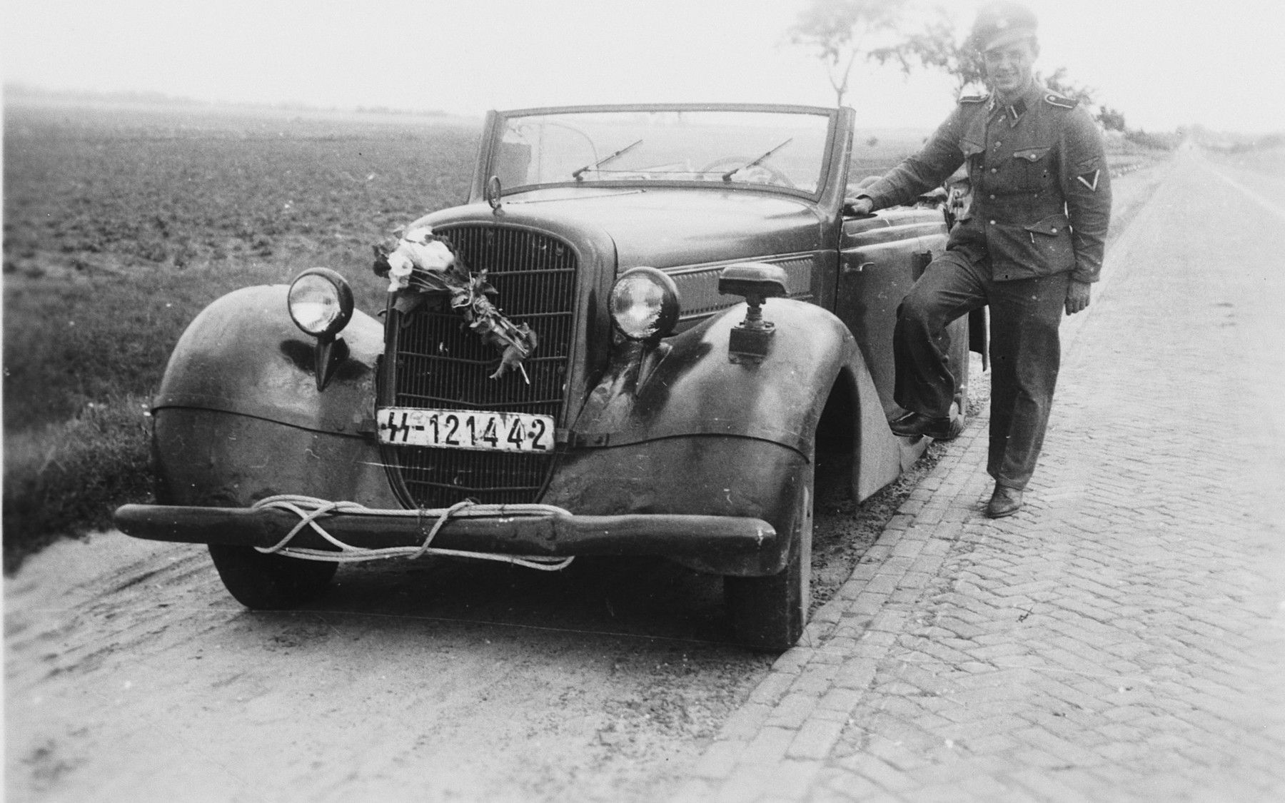 """A SS officer [perhaps Max Schmidt] stands next to an automobile with an SS lisence plate.   The caption of the SS-Archiv says """"Abschied vom Osten, auf der Fahrt ins Reich - Juli 1942"""" (Parting from east, on the trip to the """"Reich"""" July 1942)."""