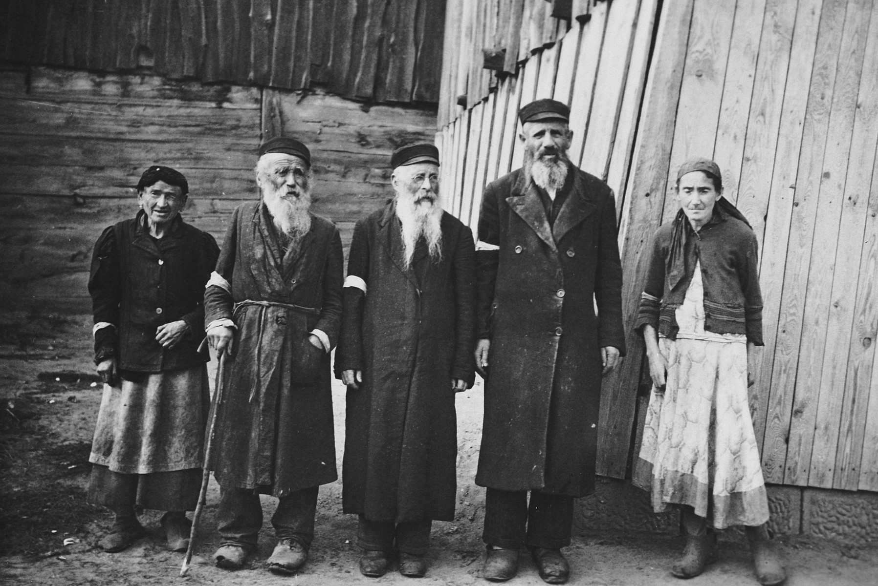 "Portrait of two older women and three older men wearing armbands standing in front of a wooden house.   The caption of the SS-Archiv says ""Original Juden in (...) Sept. 1941"" (original Jews in (...) Sept. 1941)."