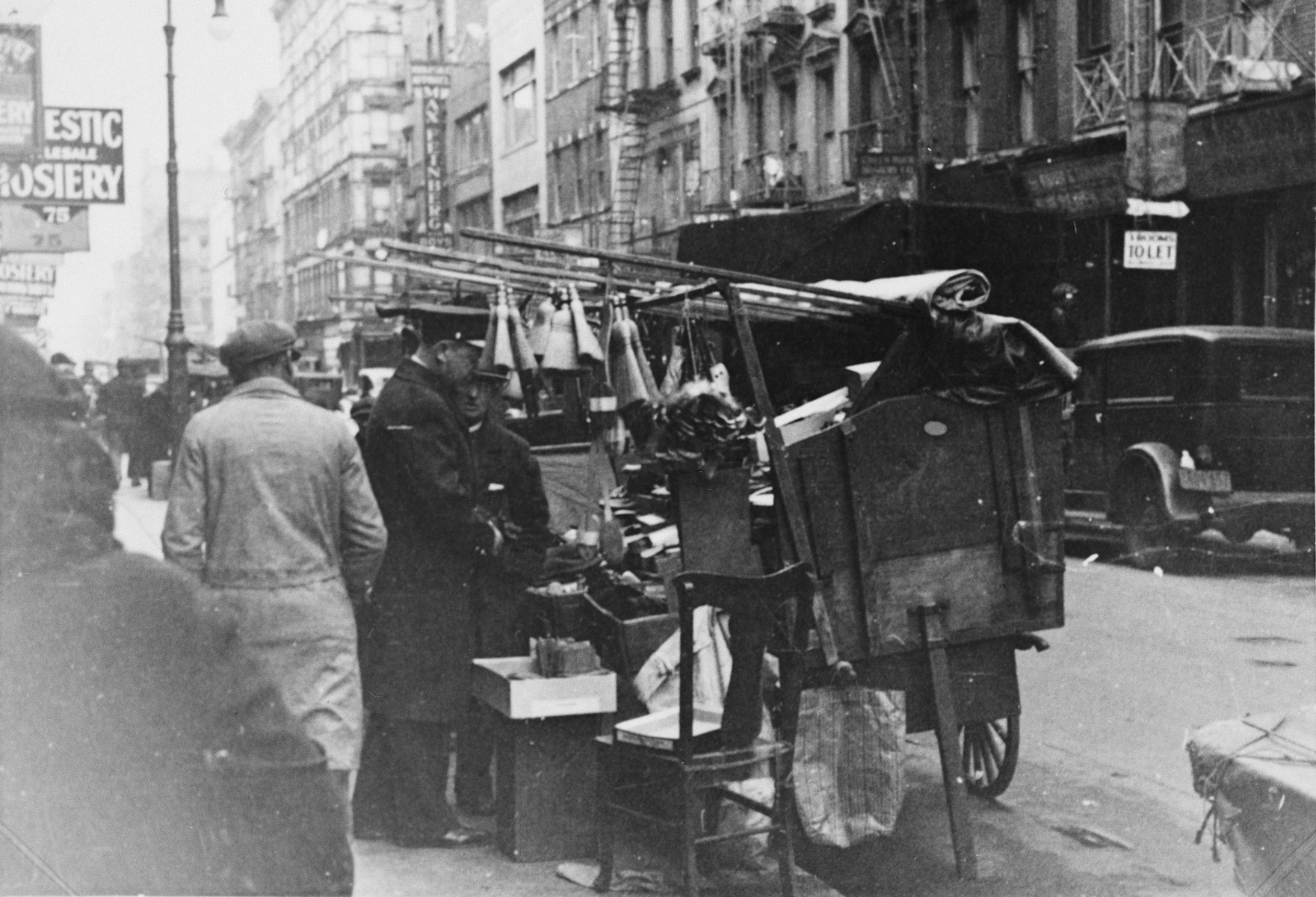 A street vendor sells his wares on a street in a Jewish neighborhood of New York City.  This photograph was taken by a German-Jew who was visiting America to determine whether or not to immigrate.
