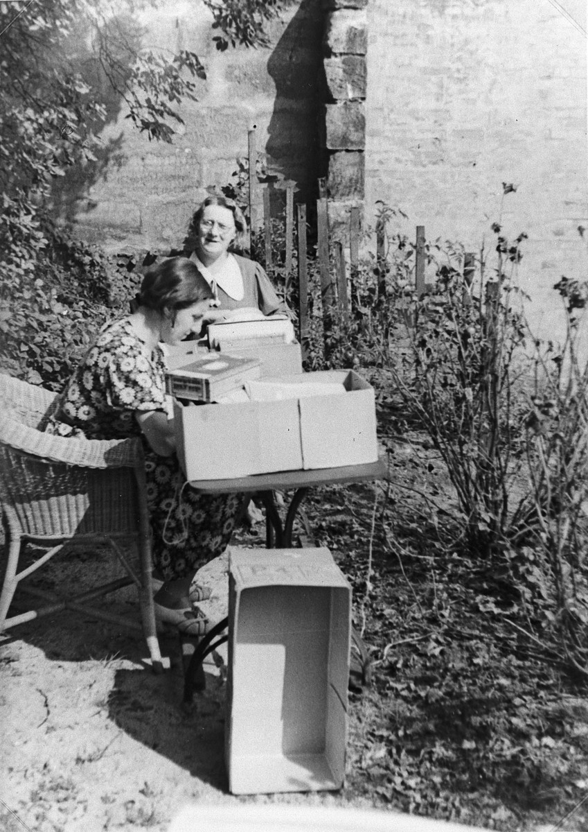 A young woman works at a table in her garden while her mother stands behind her.  Pictured writing is Lilli Bechmann Rahn.  Standing is Ida Metzger Bechmann.