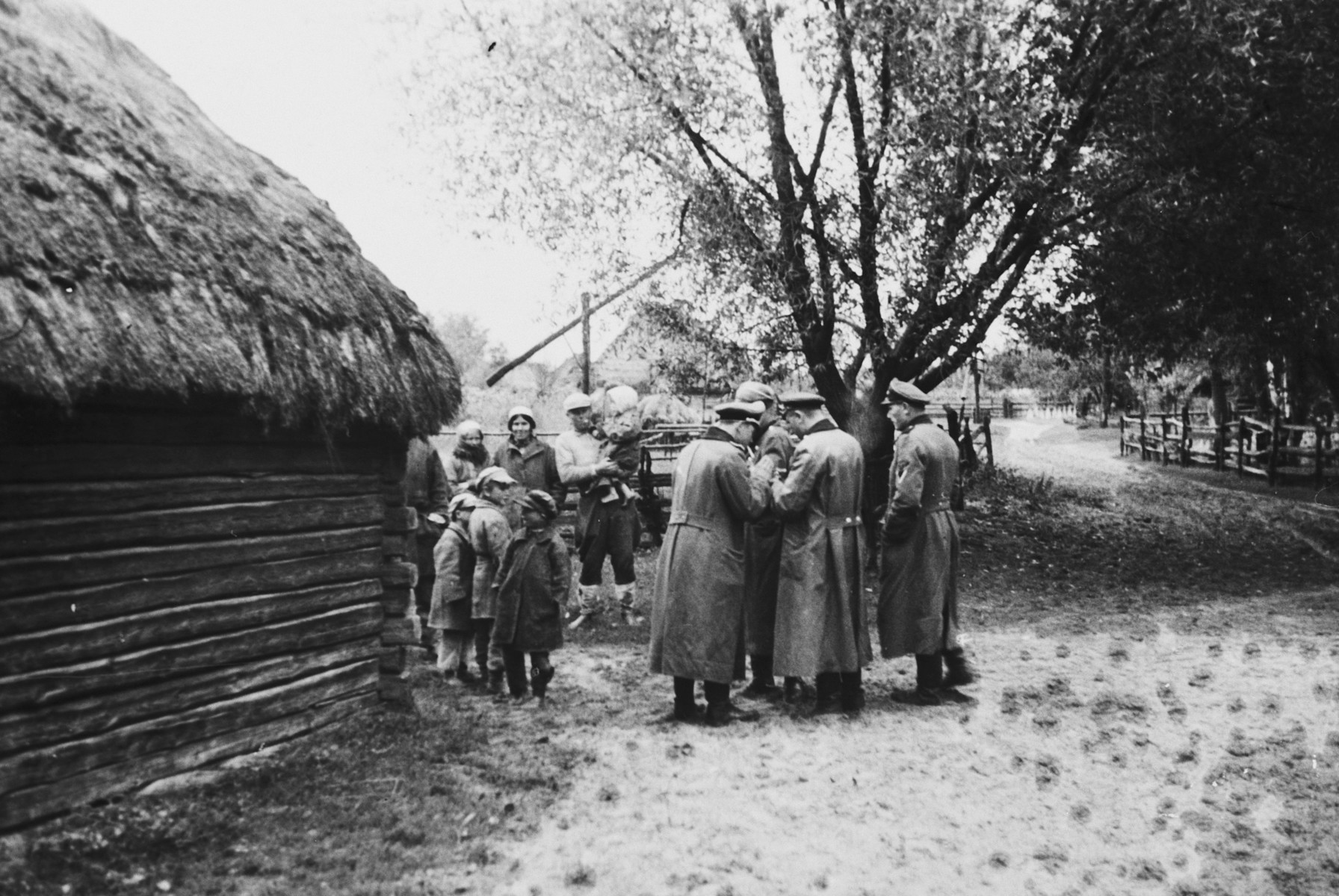 "SS officers gather outside a farmhouse in occupied Russia.    The caption of the SS-Archiv says ""Bauernhaus in der Prim Okt. 1941"" (farmhouse in the ""Prim"" Oct. 1941)."