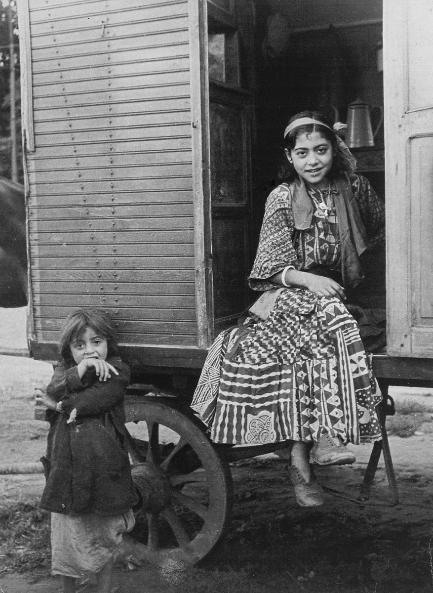 "A Roma (Gypsy) girl seated in her caravan doorway, with a young girl standing next to her.  The caption in ""The Heroic Present"" reads, ""Sinza and her little sister, Moni, Europe, 1930s."""