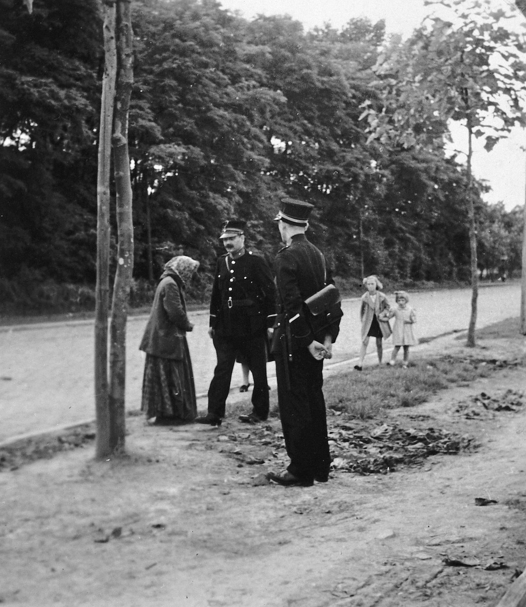 A Roma (Gypsy)? woman talks with two policemen alongside a road.