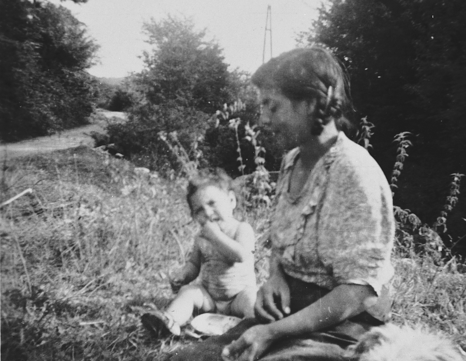A young Roma (Gypsy) woman and child seated on the grass in wartime Belgium.
