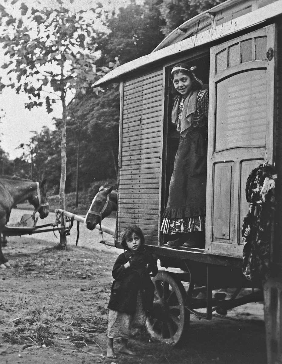 A young Roma (Gypsy) woman looks out from the doorway of a caravan, as a young child stands next to it.