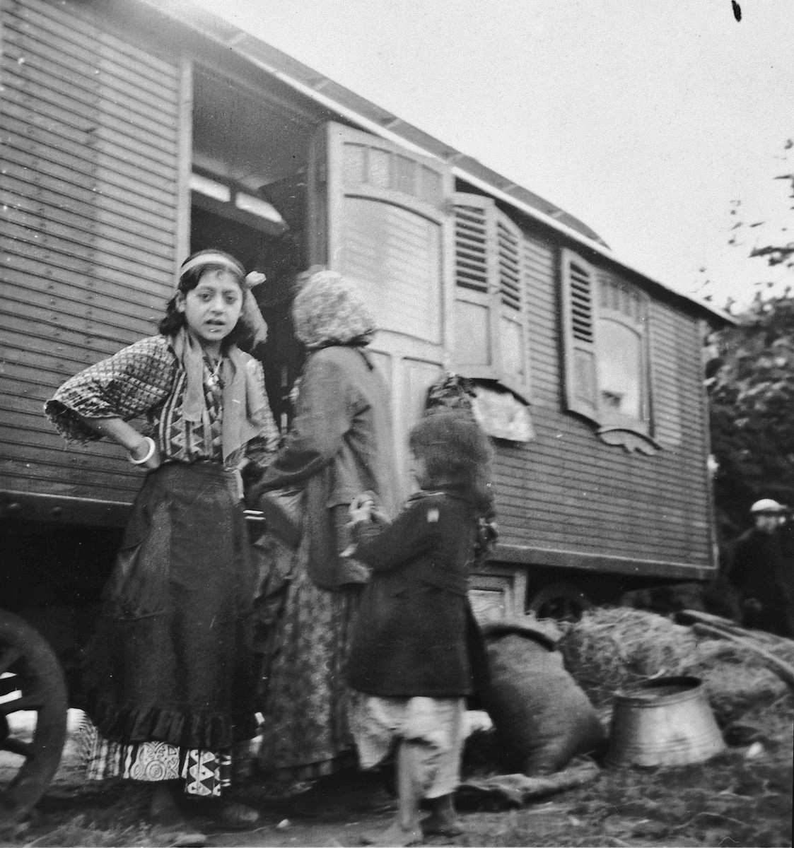 Roma (Gypsy) women and children standing outside a caravan.