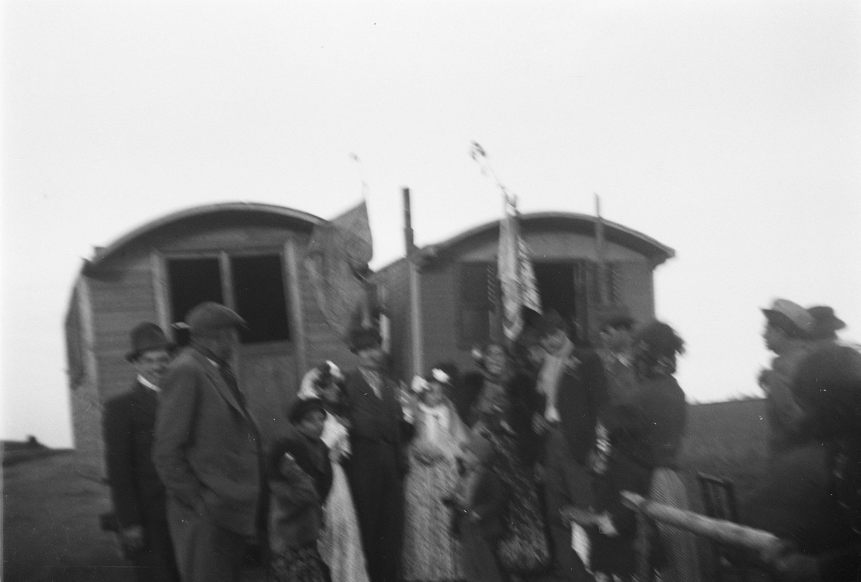 A group of Roma (Gypsies) gather in front of two caravans adorned with banners, possibly for a wedding.