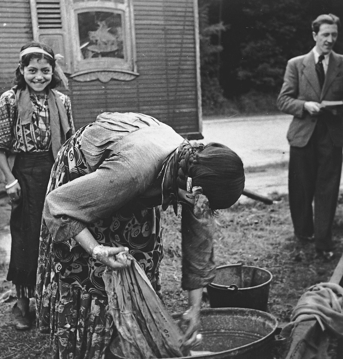 A Roma (Gypsy) woman washes clothing in a tub, as a young girl smiles in the background.
