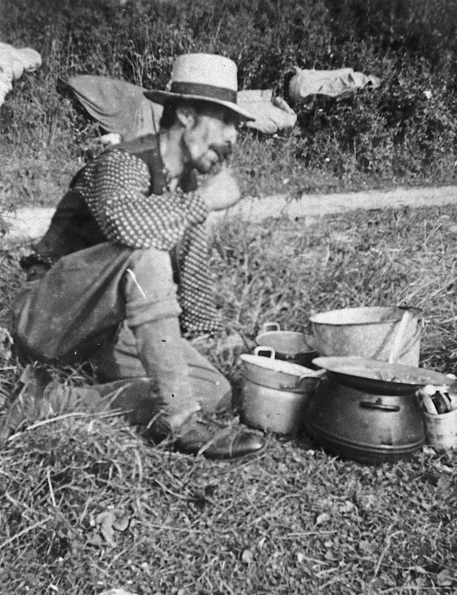 A Roma (Gypsy) man, seated on the ground next to a group of cooking pots.