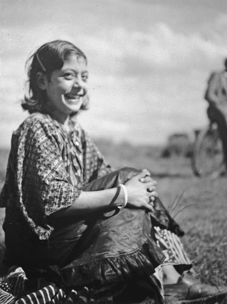 A smiling Roma (Gypsy) girl sits with hands clasped in front of her knees.