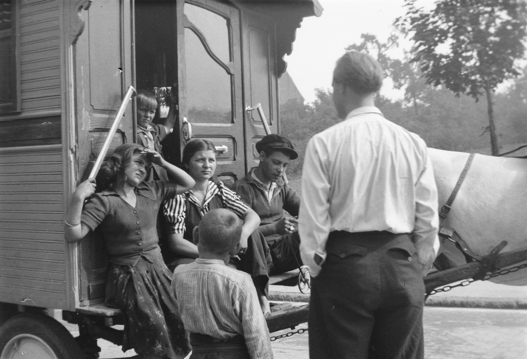 "A group of Roma (Gypsy) children gathered around the entrance to a caravan visit with with their friend, Jan Yoors (with back to the camera).  The caption in ""The Heroic Present"" reads, ""Jan Yoors (back to camera) and Lovara friends, Europe, 1930s."""