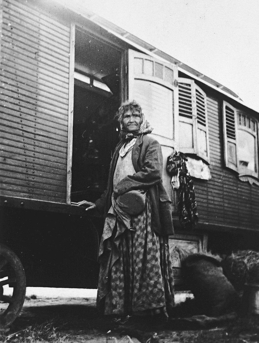 A Roma (Gypsy) woman stands outside a caravan.