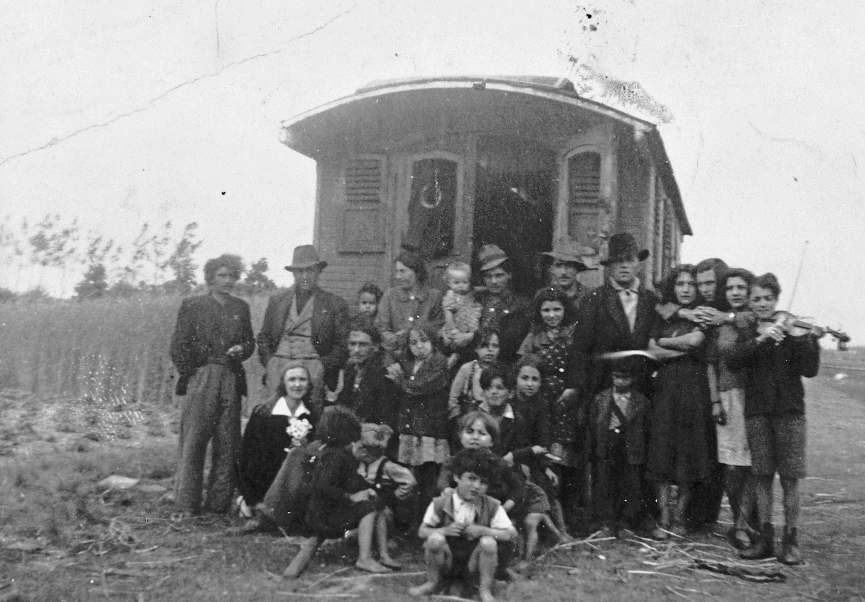 A group of Roma (Gypsies) poses in front of a caravan.