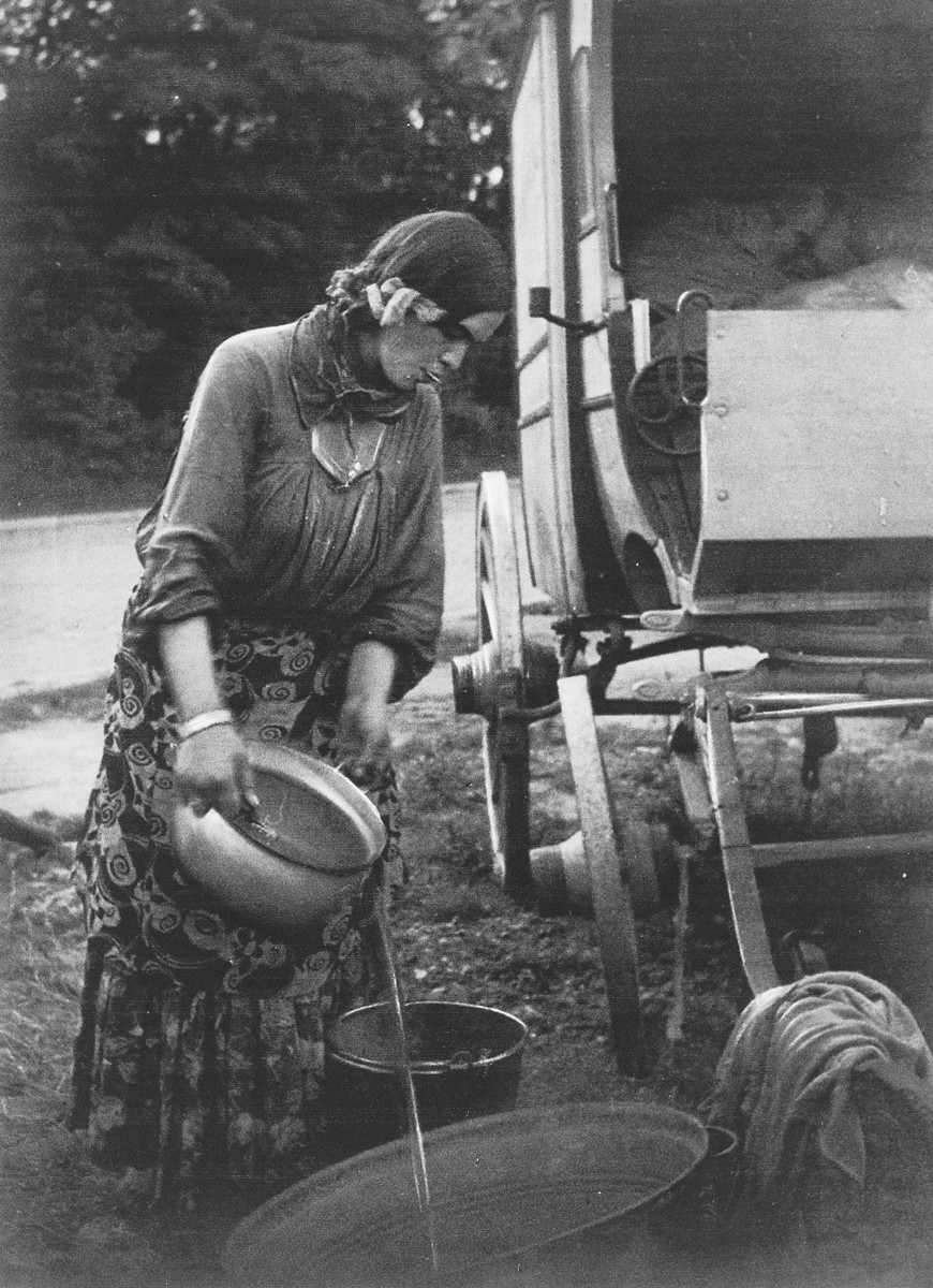 """A Roma (Gypsy) woman standing next to her caravan pours water from a pot into a laundry tub.  The caption in """"The Heroic Present"""" reads, """"Lovara woman, 1934."""""""