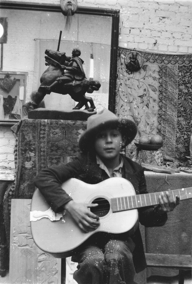A Romani boy plays a guitar in front of a sculpture created by Jan Yoors.