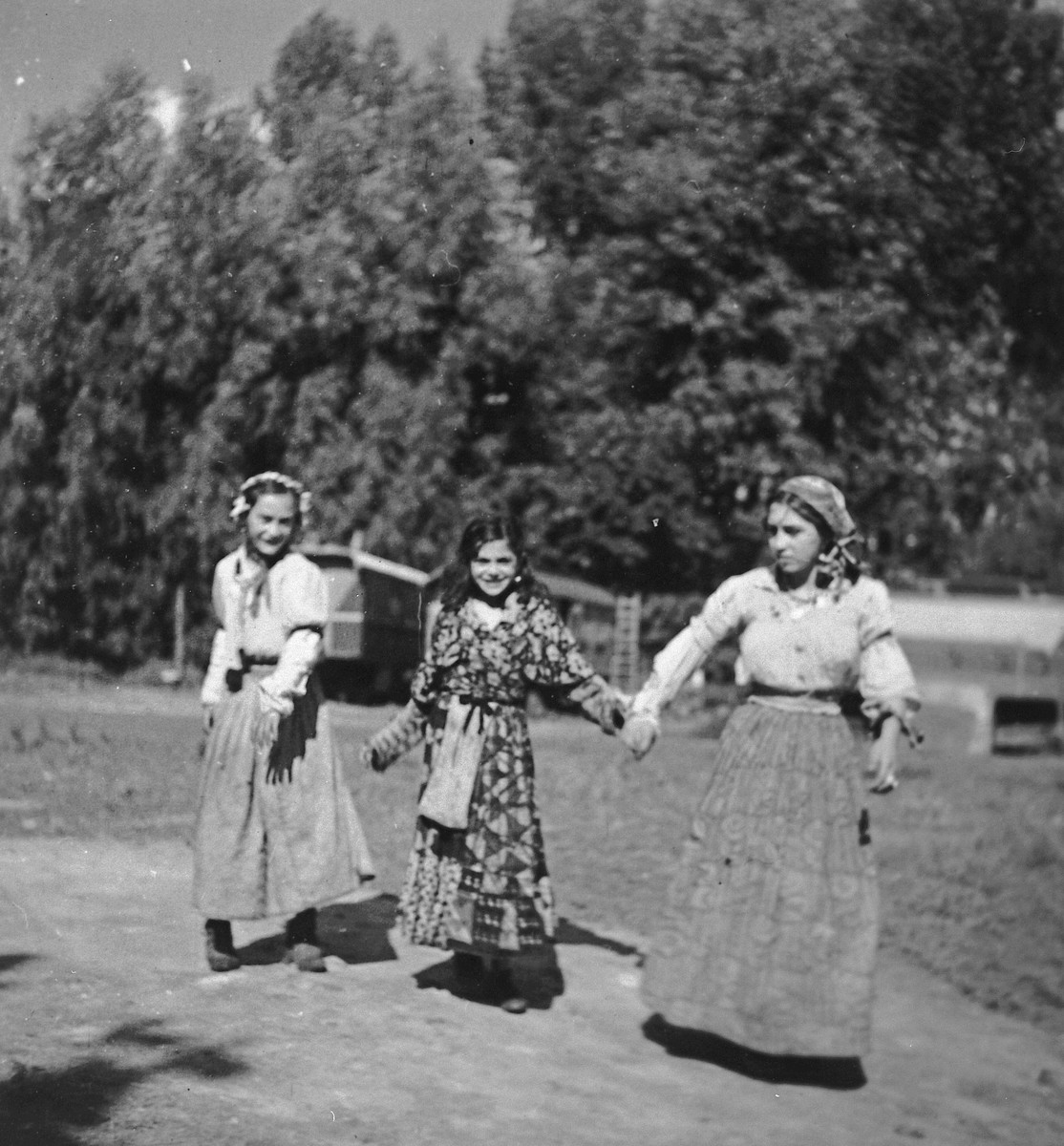 "Three young Roma (Gypsy) women walk together along a road.  The caption in ""The Heroic Present"" reads, ""Europe, 1930s."""