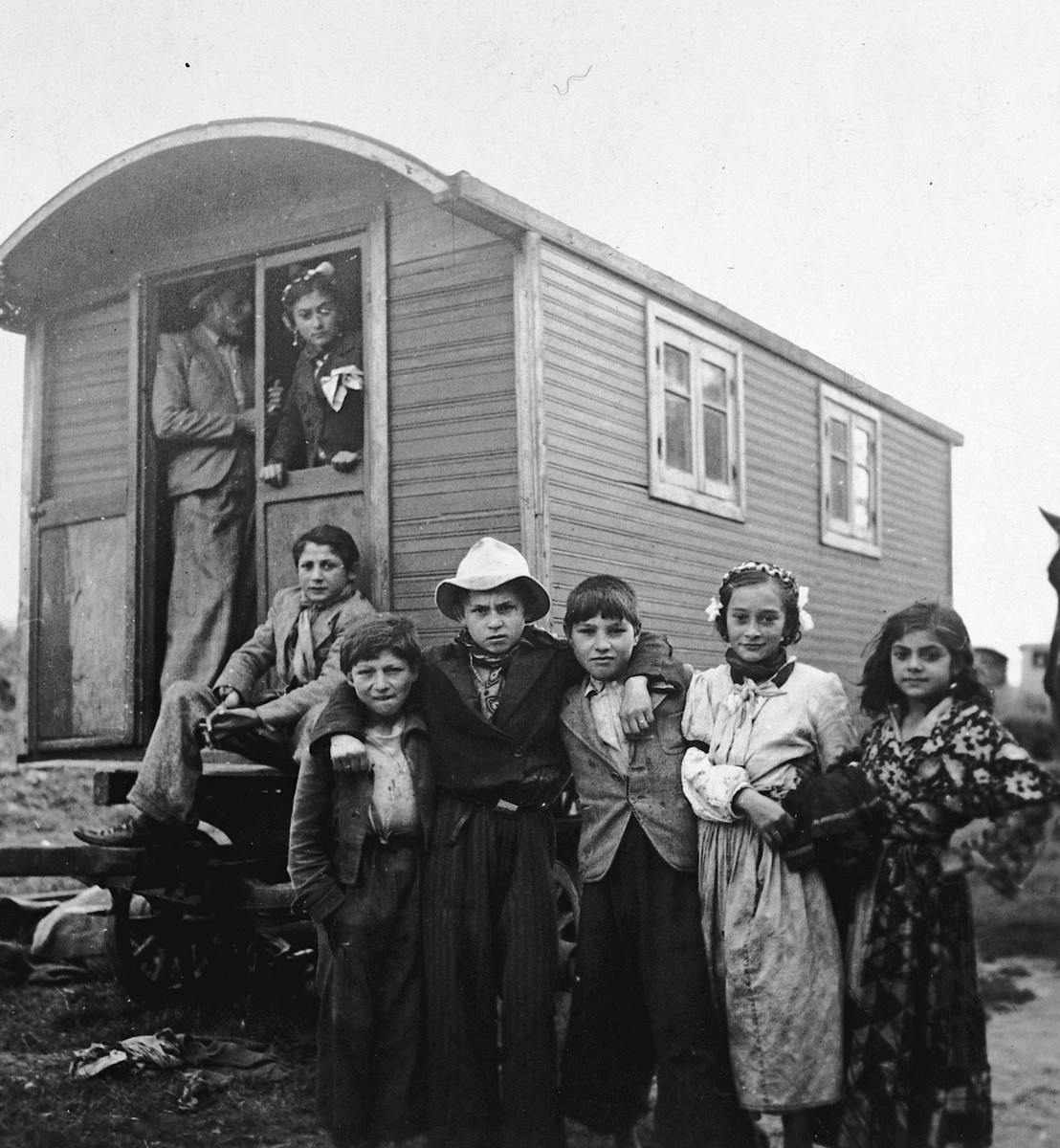 "Roma (Gypsy) children pose near a caravan, as adults look out from the doorway.  The caption in ""The Heroic Present"" reads, ""Europe, 1930s."""