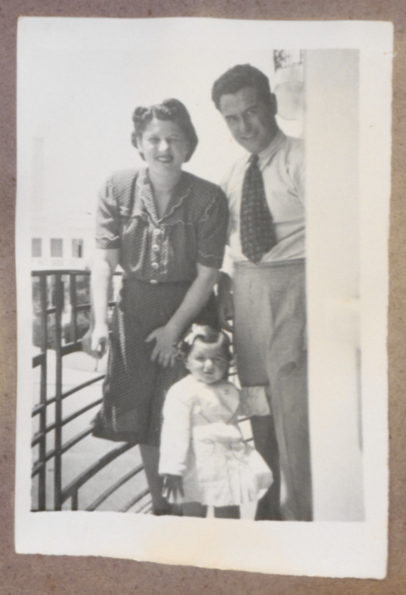 Photo album page showing Daisy Breuer in arms of her mother (Lilly Breuer) and father (Dr. Theodore Breuer) on balcony of apartment Muhammed V Blvd,,Tangiers.