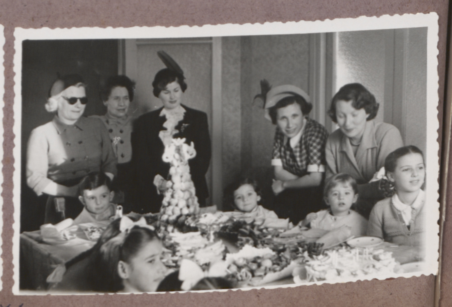 Photo album page showing Daisy Breuer's 7th birthday party with many Hungarian Jewish survivor children in attendance.