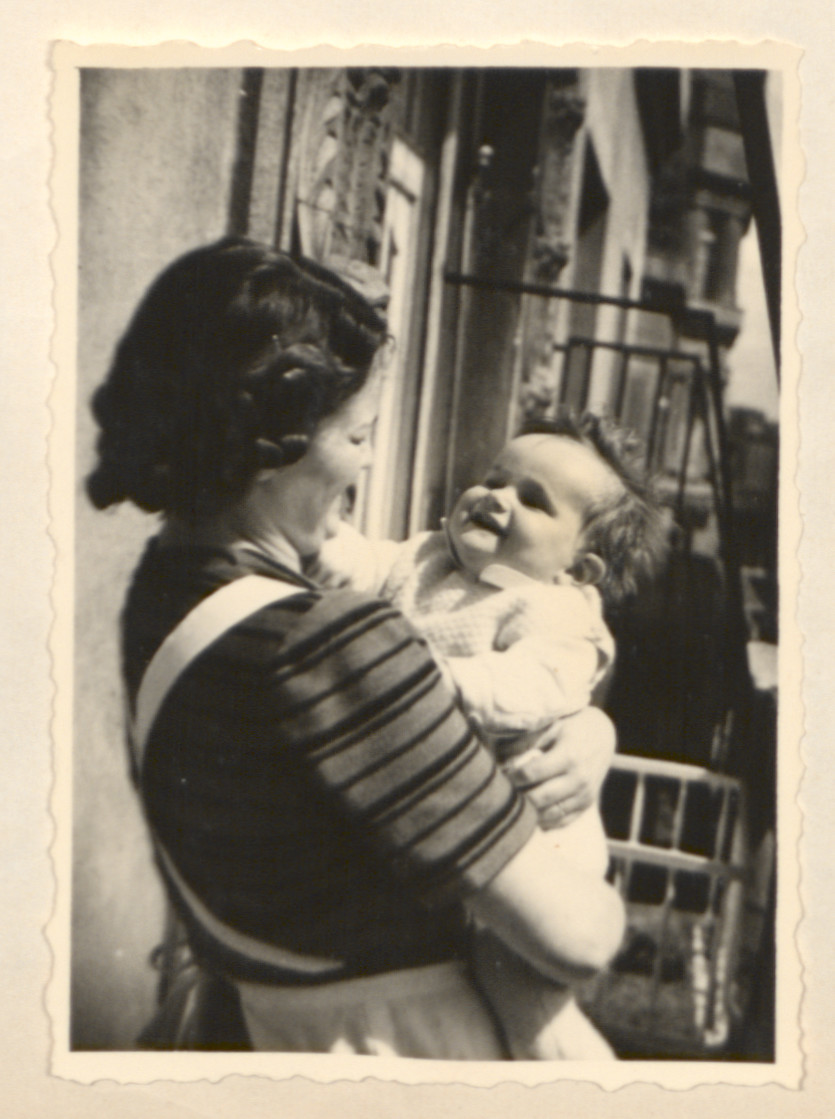 Page from a baby book showing Ernestine (Ily) Merei holding her infant son John on their balcony.