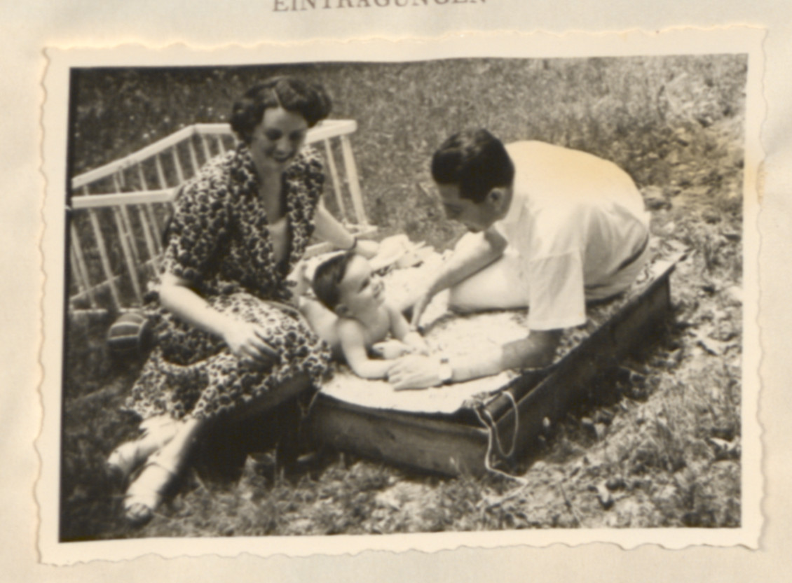 Page from a baby album showing Ernest (Erno) and Ernestine (Ily) Merei playing outdoors with their infant John.