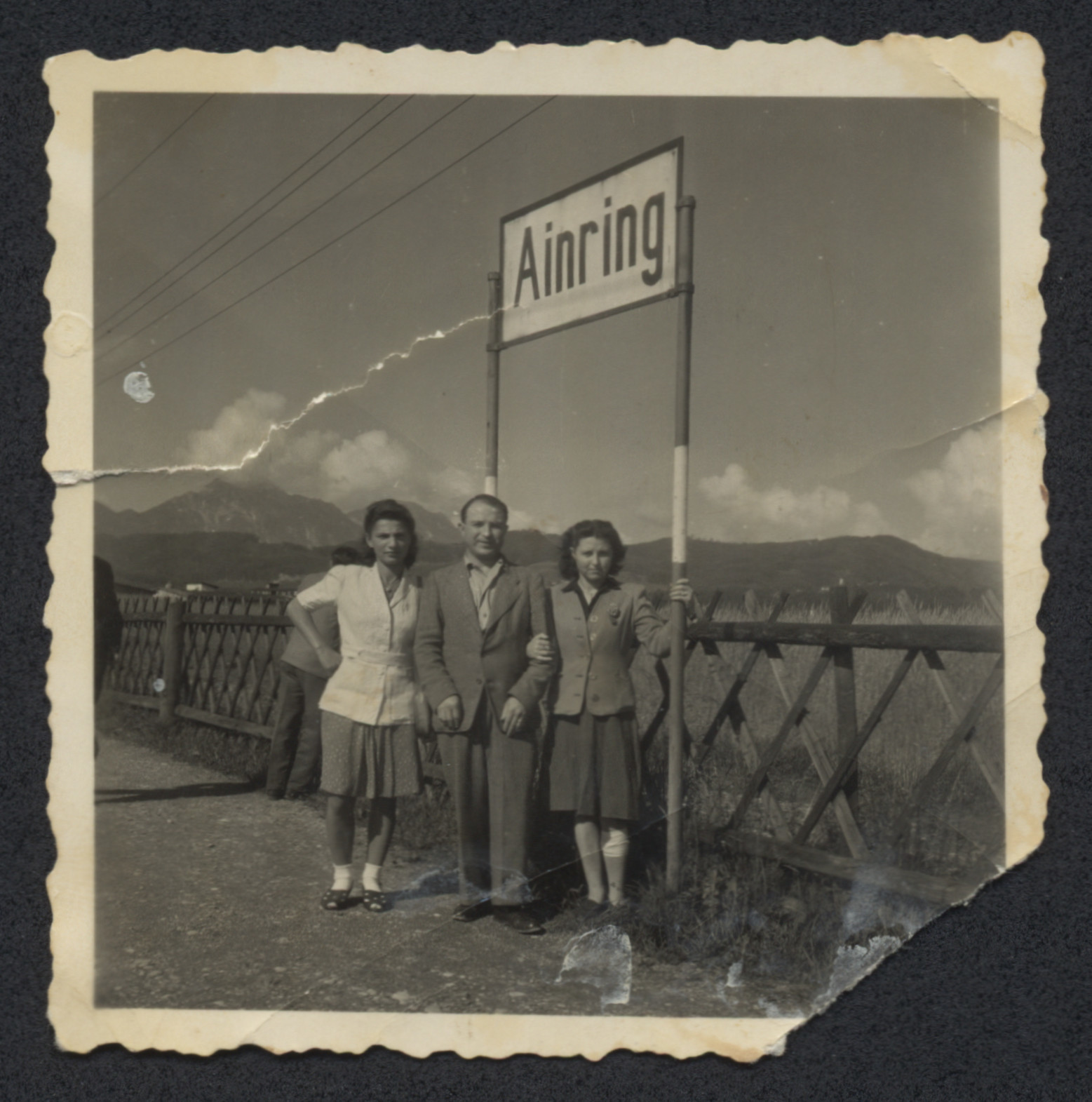Hencia Wagner poses with two friends by the entrance of the Ainring displaced persons camp.
