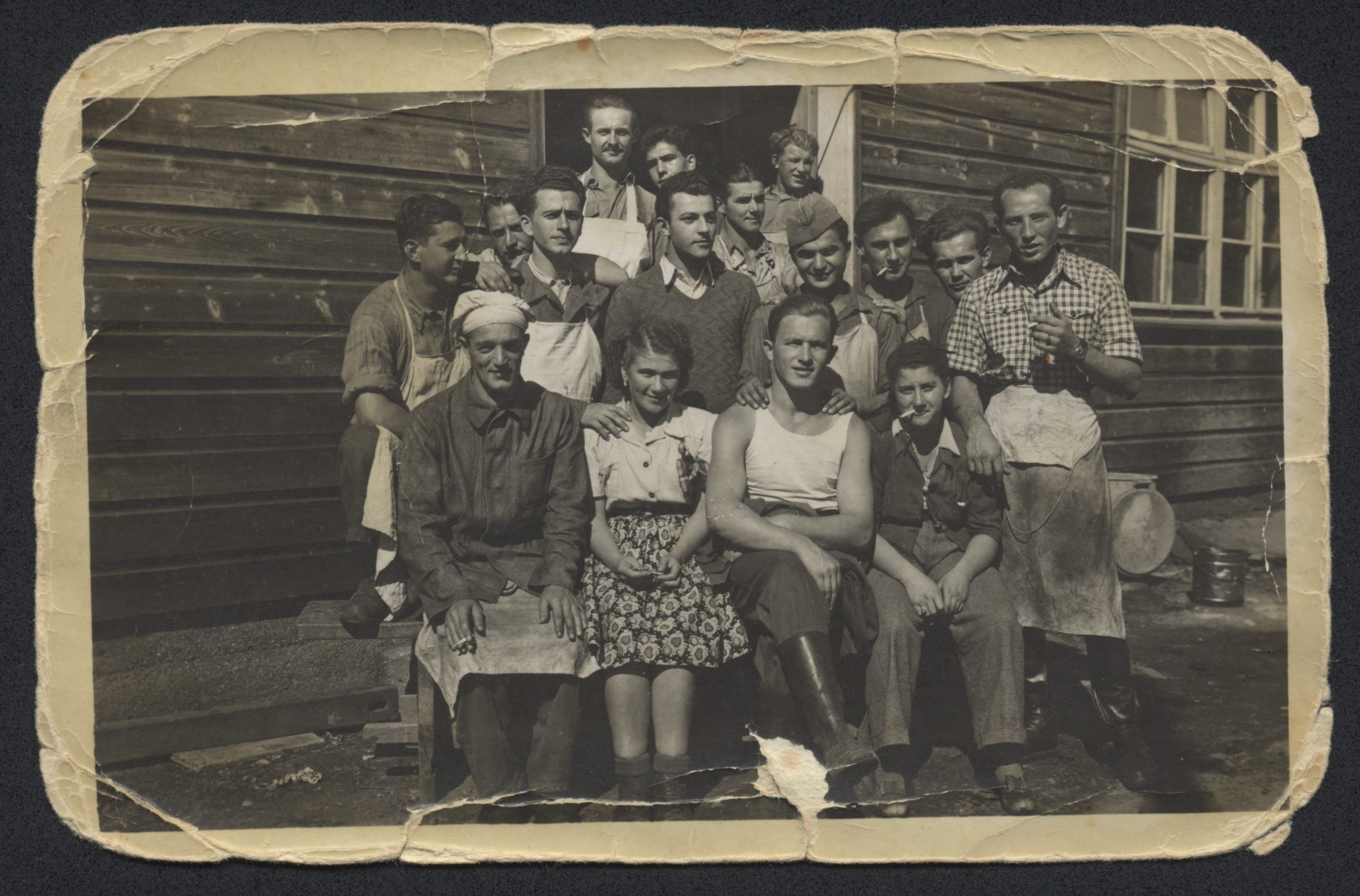 Group portrait of men and women, many wearing cook's aprons, pose outside a wooden barrack in the Bindermichl displaced persons camp.  William Abraham is in the center wearing a cap.  He worked in the camp kitchen.