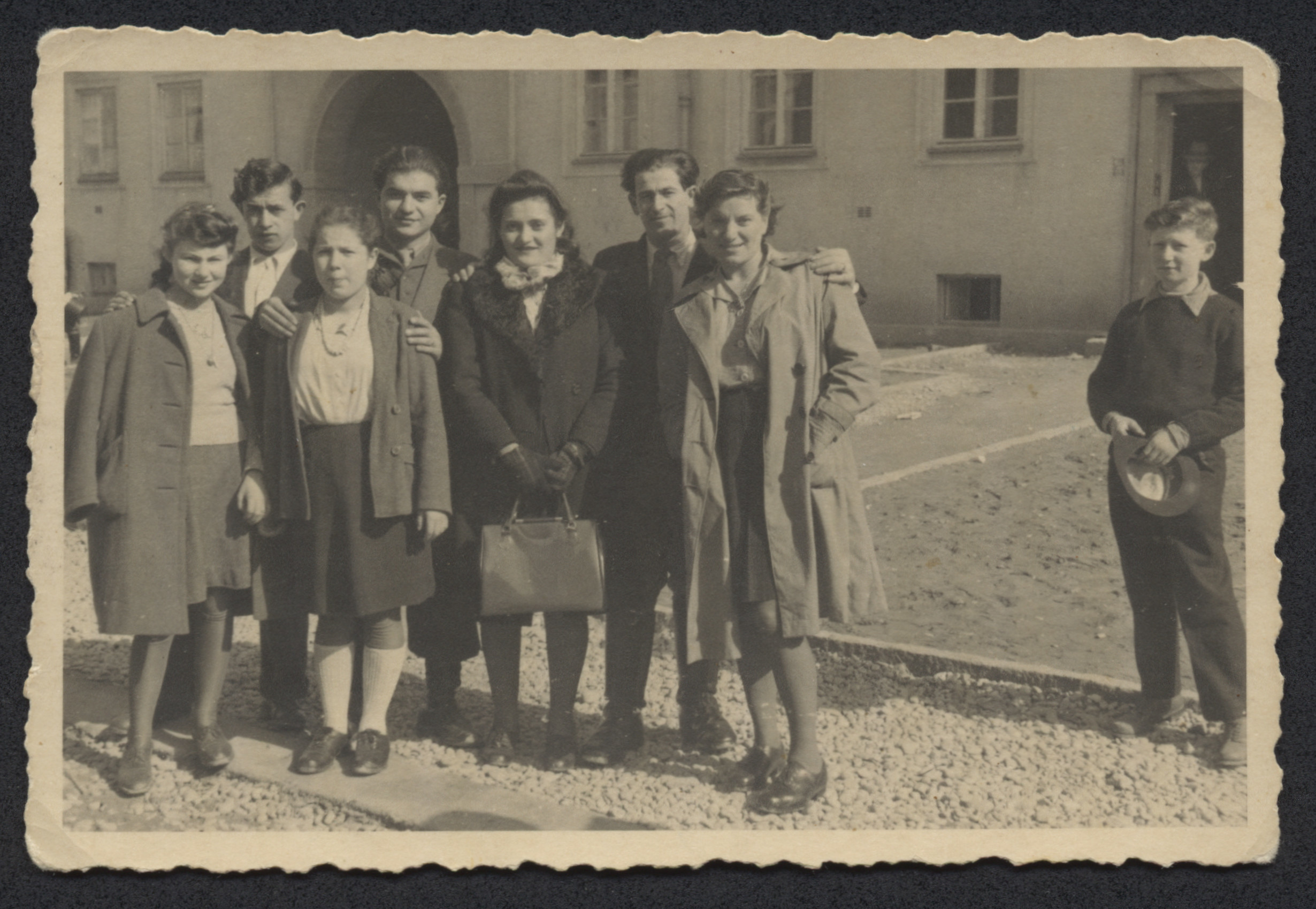 Group portrait of men and women in the Bindermichl displaced persons camp.  Among those pictured are William Abraham (fourth from the left.  His brother-in-law Simon Wizel is second from the right  with his arm around his wifeTzivya Abraham Wizel.