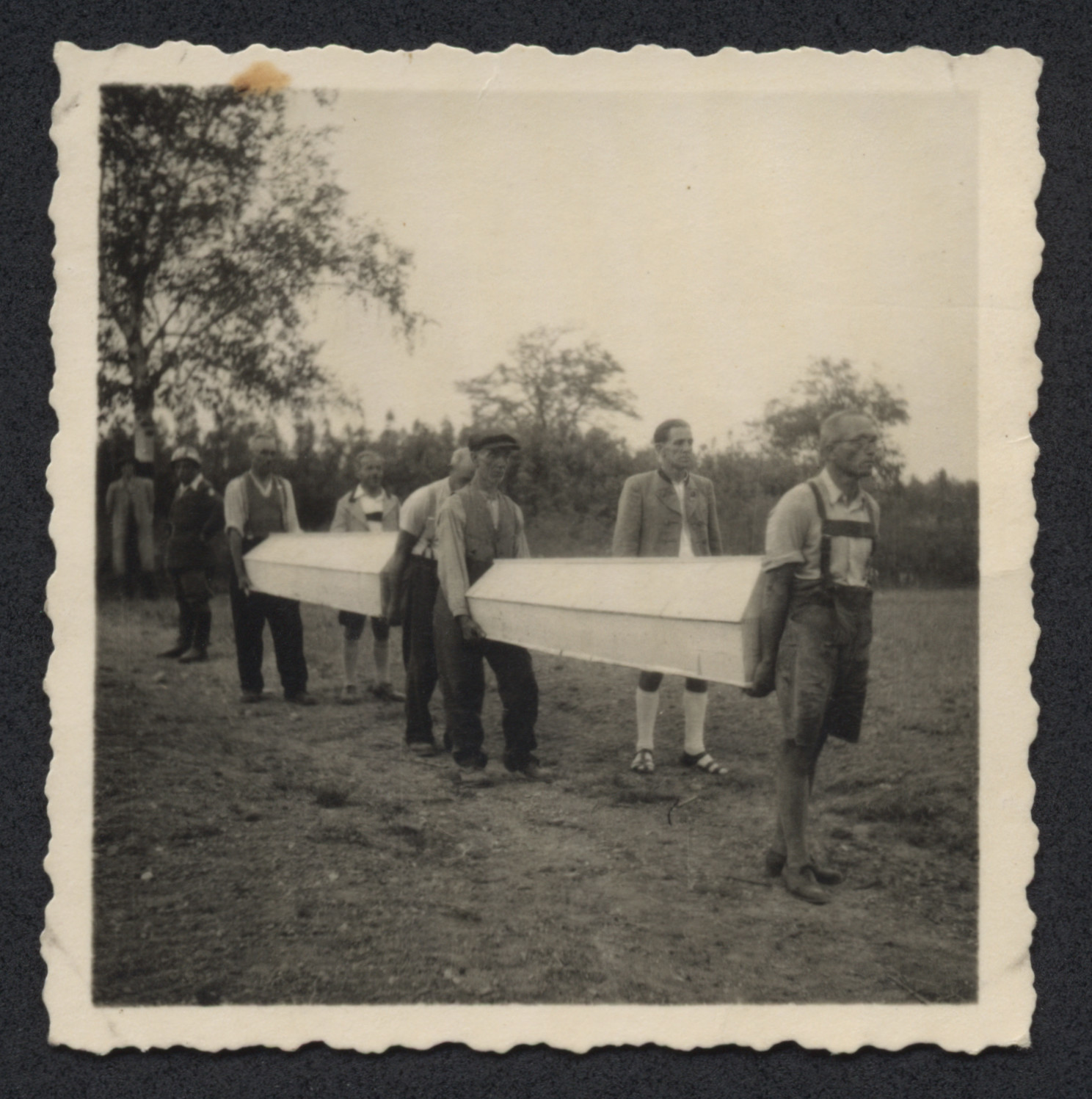 Austrians carry wooden coffins in [what probably is a postwar reburial of Holoocaust victims.]
