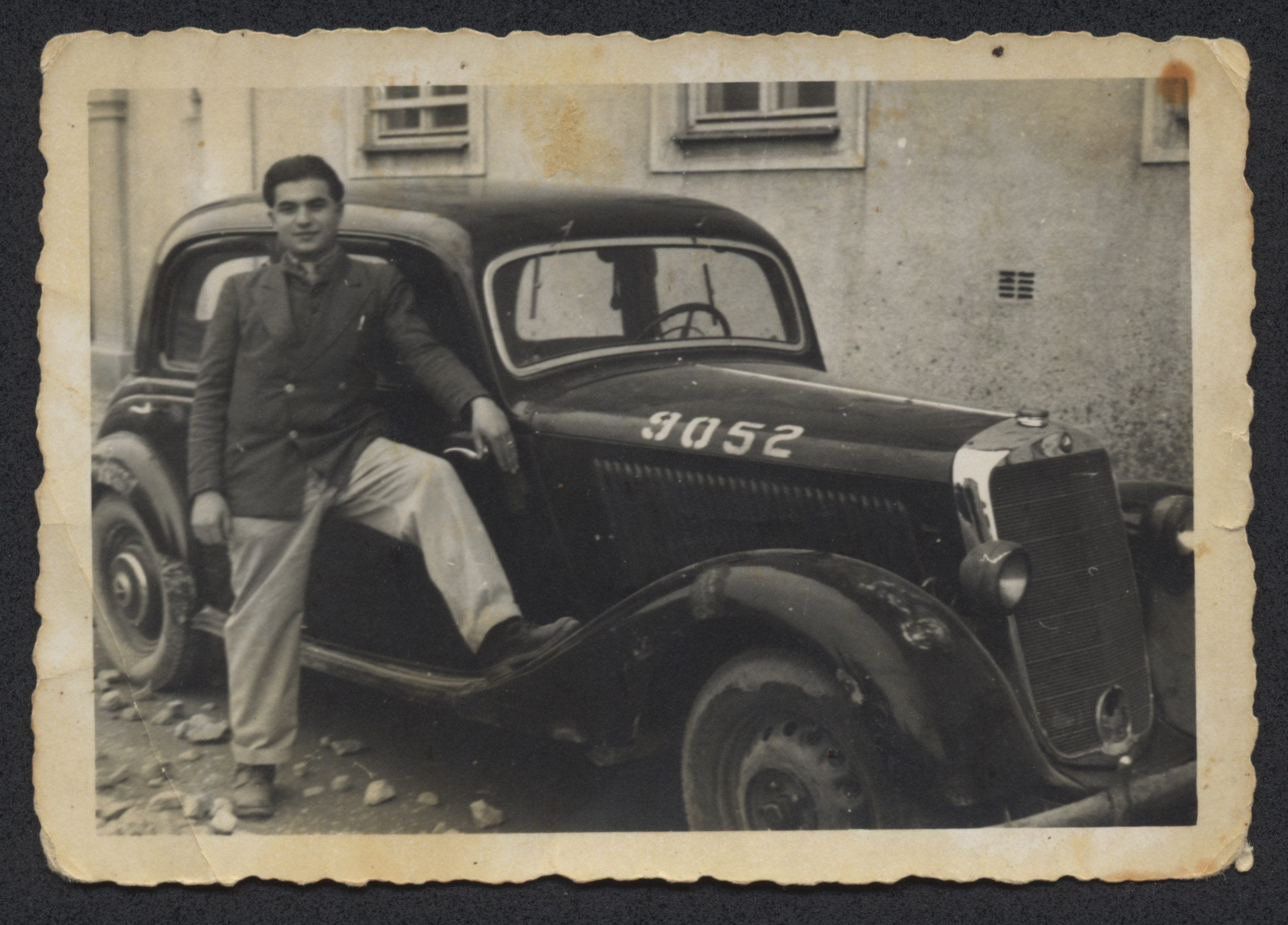 William Abraham poses next to an automobile in the Bindermichl displaced persons camp.