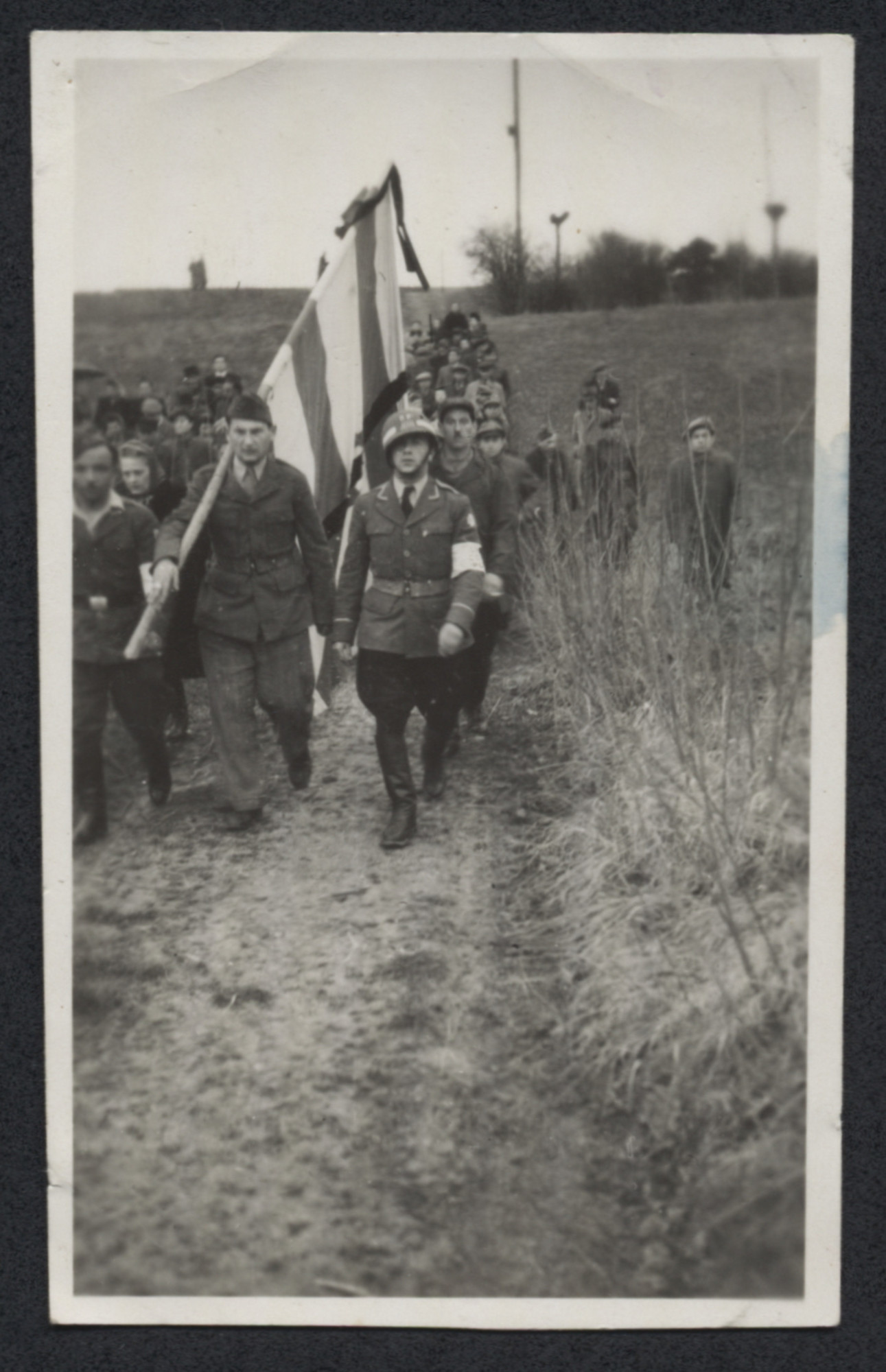 Displaced persons march carrying a flag or banner.