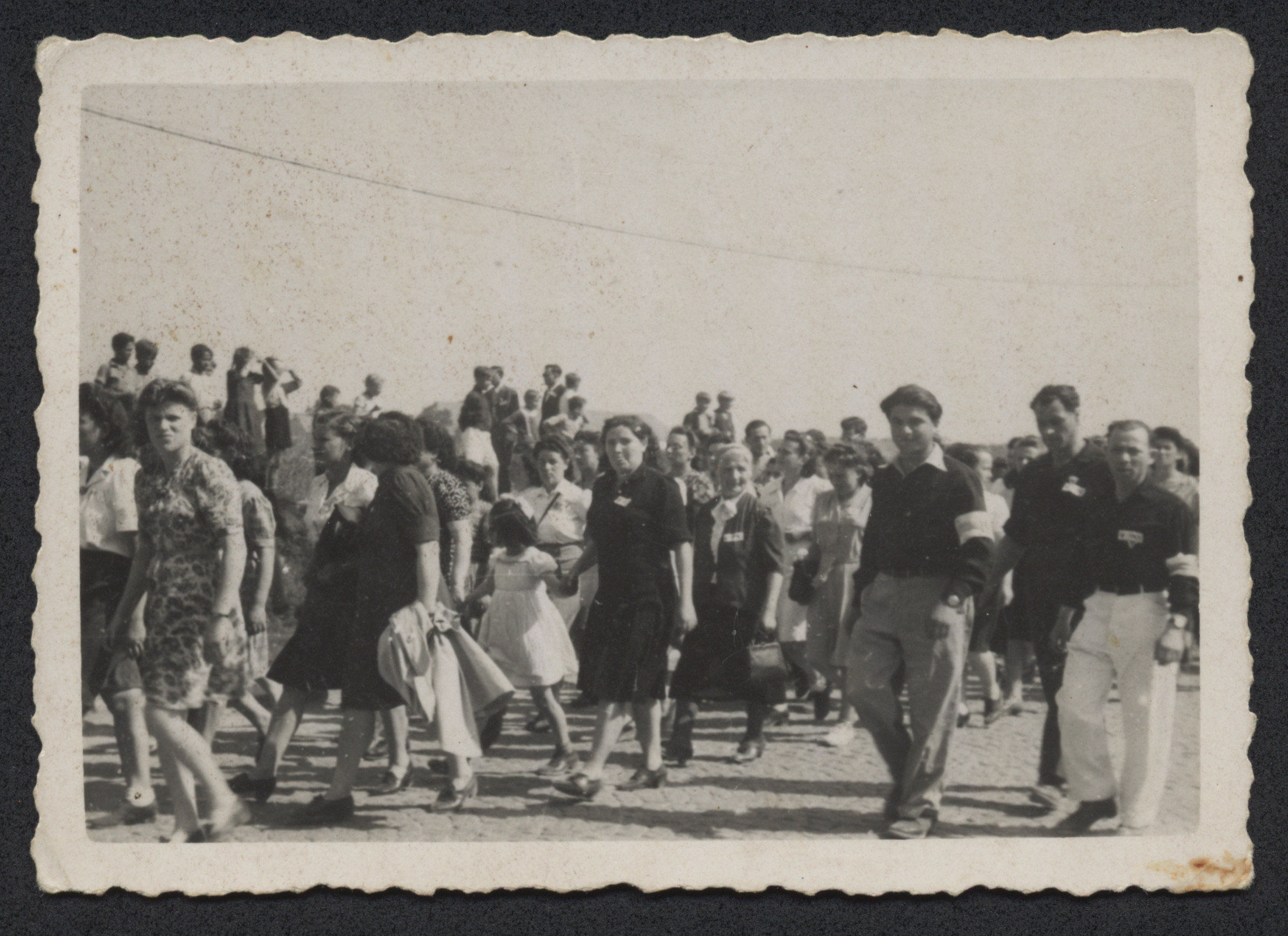Men and women march [in what probably is a Zionist demonstration] in the Bindermichl displaced persons camp.  William Abraham is third from the right with an armband.