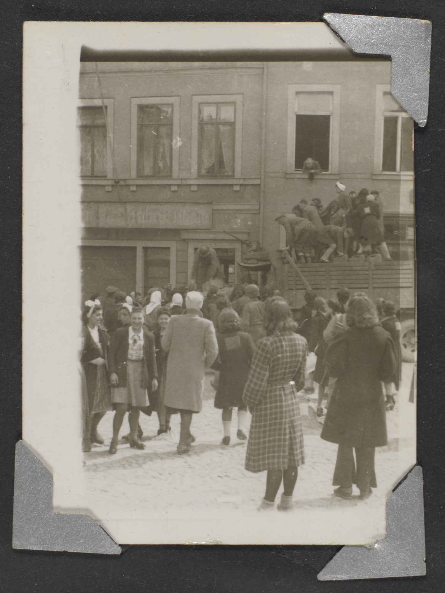 Hungarian refugees gather in the street in Waldenburg.  Original Caption: Nice clothes were no doubt liberated previous to time picture was taken. Refugees in Waldenberg. April 1945.