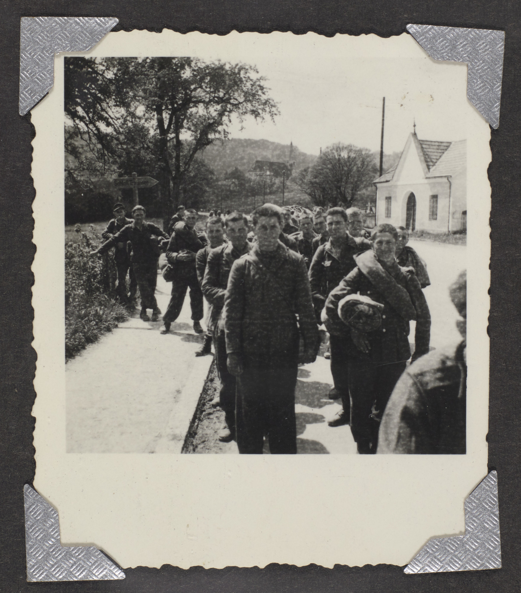 "A group of  Germans walk down a street.  The original caption reads: ""Germans coming out from the hills after V.E. Day."""