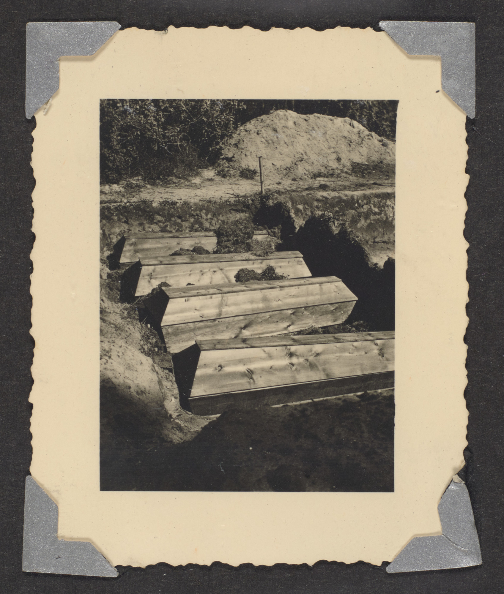 "A row of coffins is prepared for burial in a mass grave.  the original caption reads: ""Unfinished, mass graves"""
