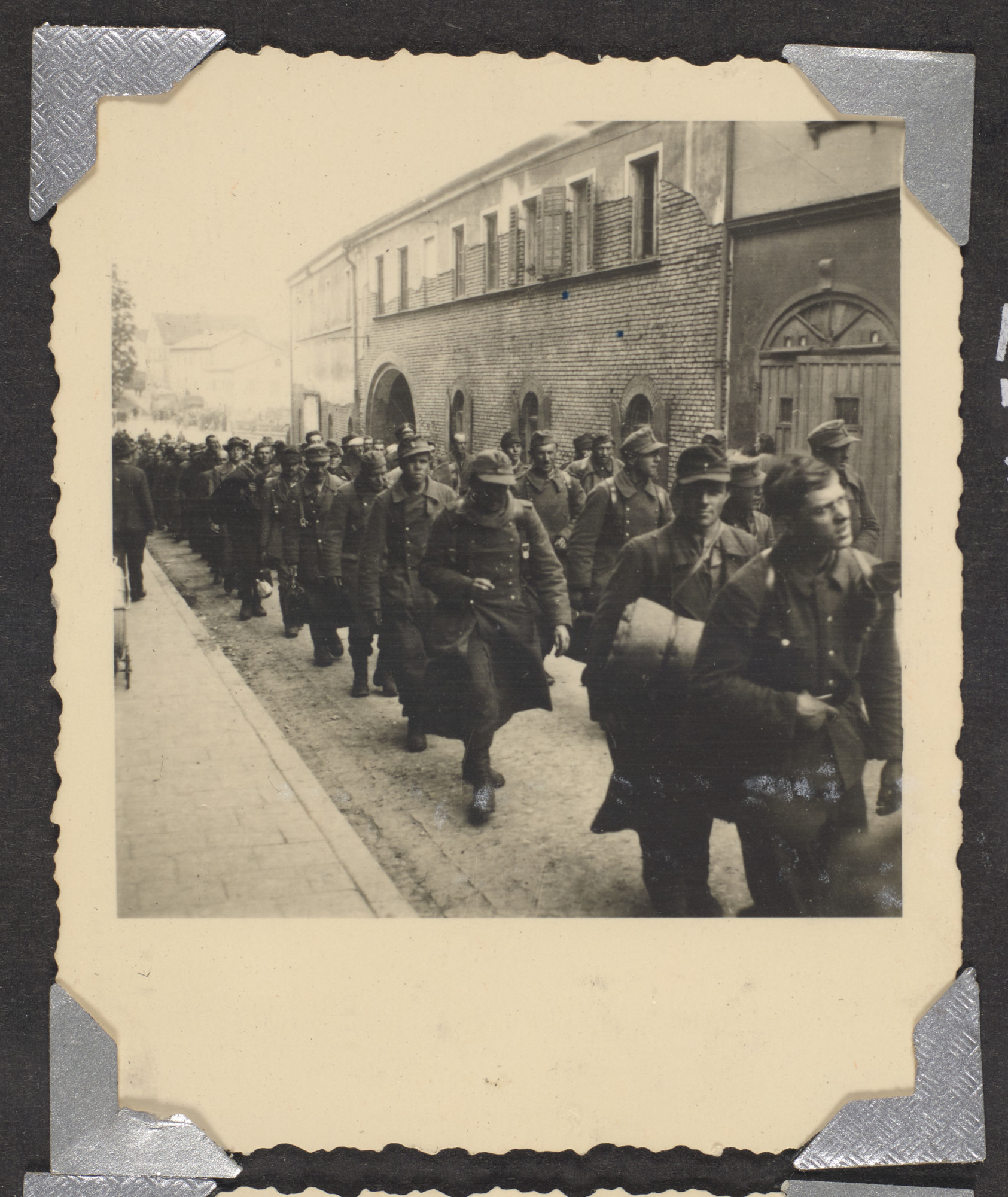 A column of freed POWs march through a street.   Original Caption: Isar River at Sinback, Germany. April 1945.