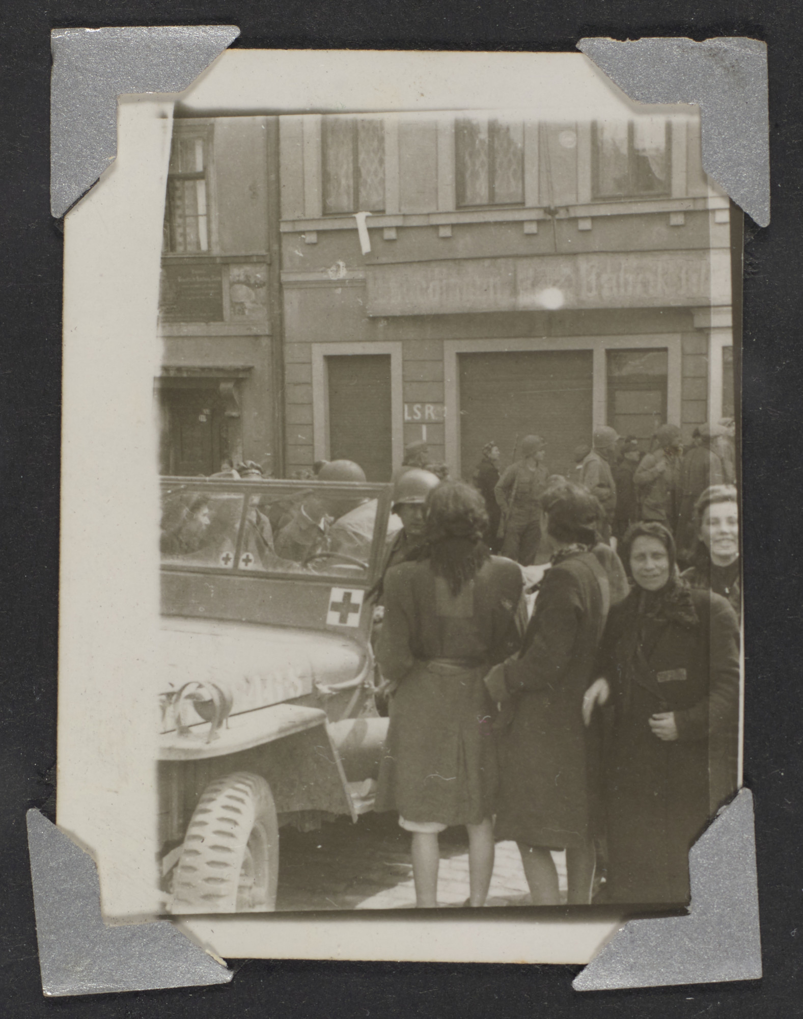 A group of refugees gather on a street in Waldenberg next to Louis Bernard Katz's Jeep.   Original caption: Refugees and my jeep in Waldenberg. Note patch on back--mark of forced labor. April 1945.