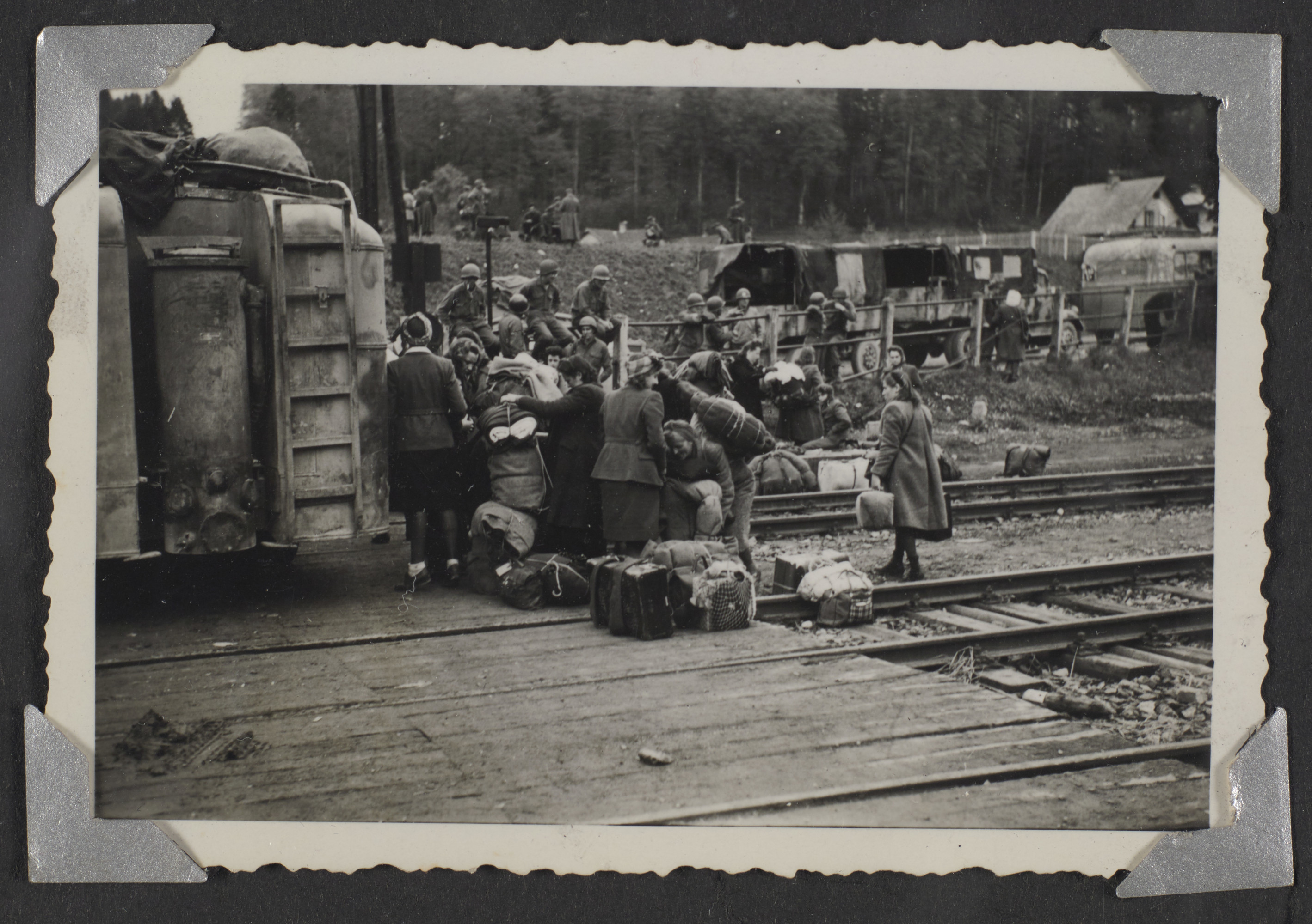 "A group of people with their luggage  gather at a railroad station accompanied by soldiers  The original caption reads: ""Railroad station wehre German Prisoners of War were loaded on trains."""